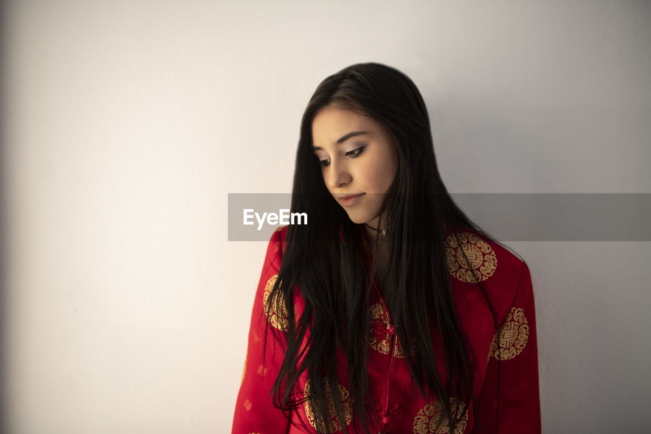 young women, young adult, one person, front view, standing, indoors, wall - building feature, long hair, beauty, hair, beautiful woman, waist up, hairstyle, lifestyles, red, copy space, looking, casual clothing, teenager, contemplation