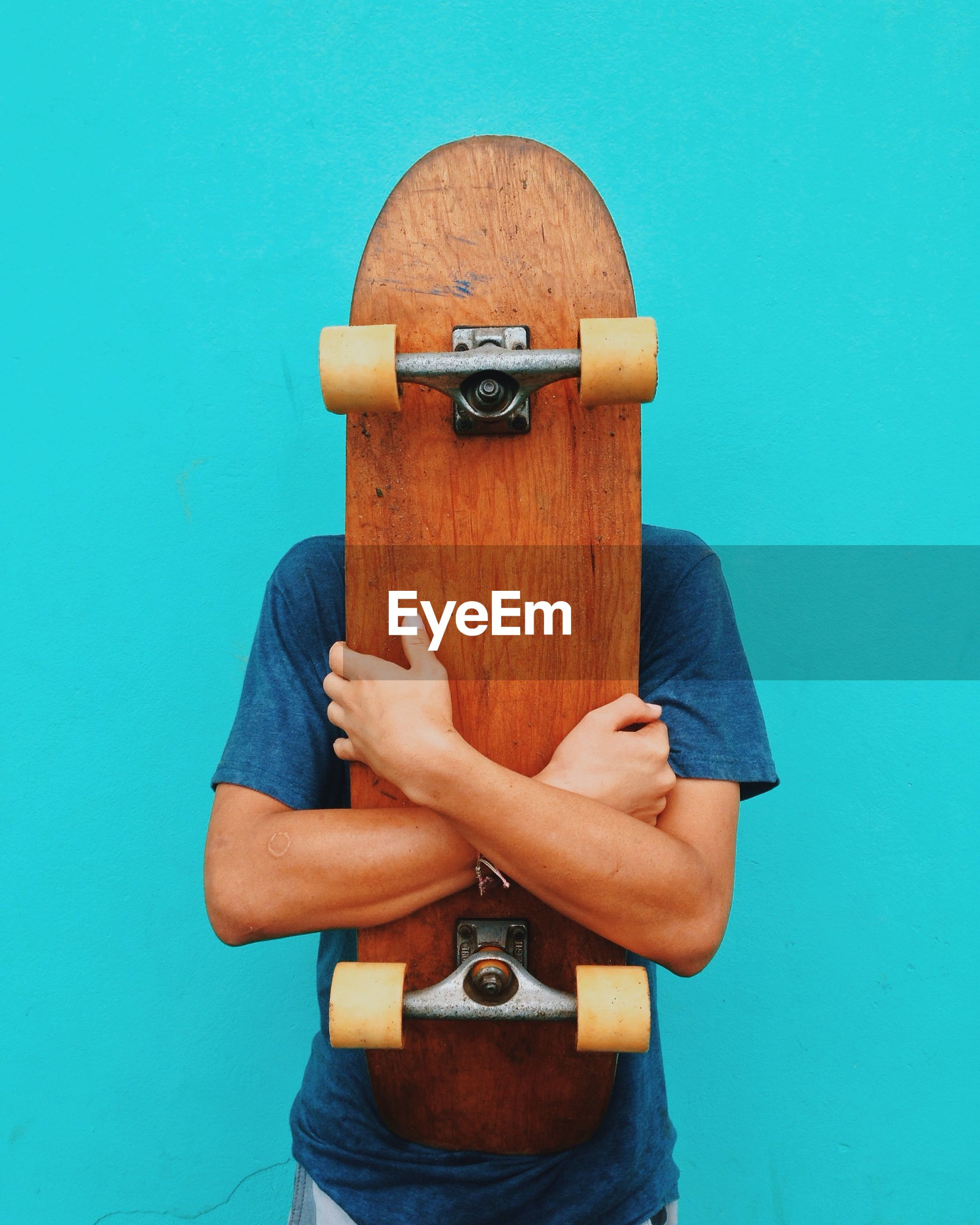Man holding skateboard against turquoise wall