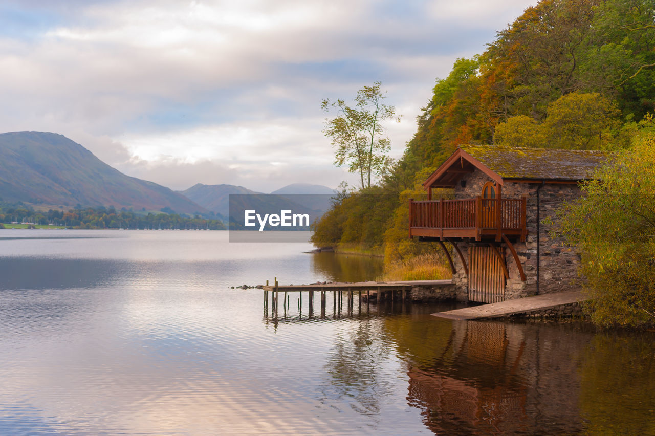 mountain, water, built structure, architecture, cloud - sky, beauty in nature, scenics - nature, sky, tree, lake, plant, building exterior, nature, reflection, house, no people, tranquil scene, tranquility, building, mountain range, outdoors, cottage
