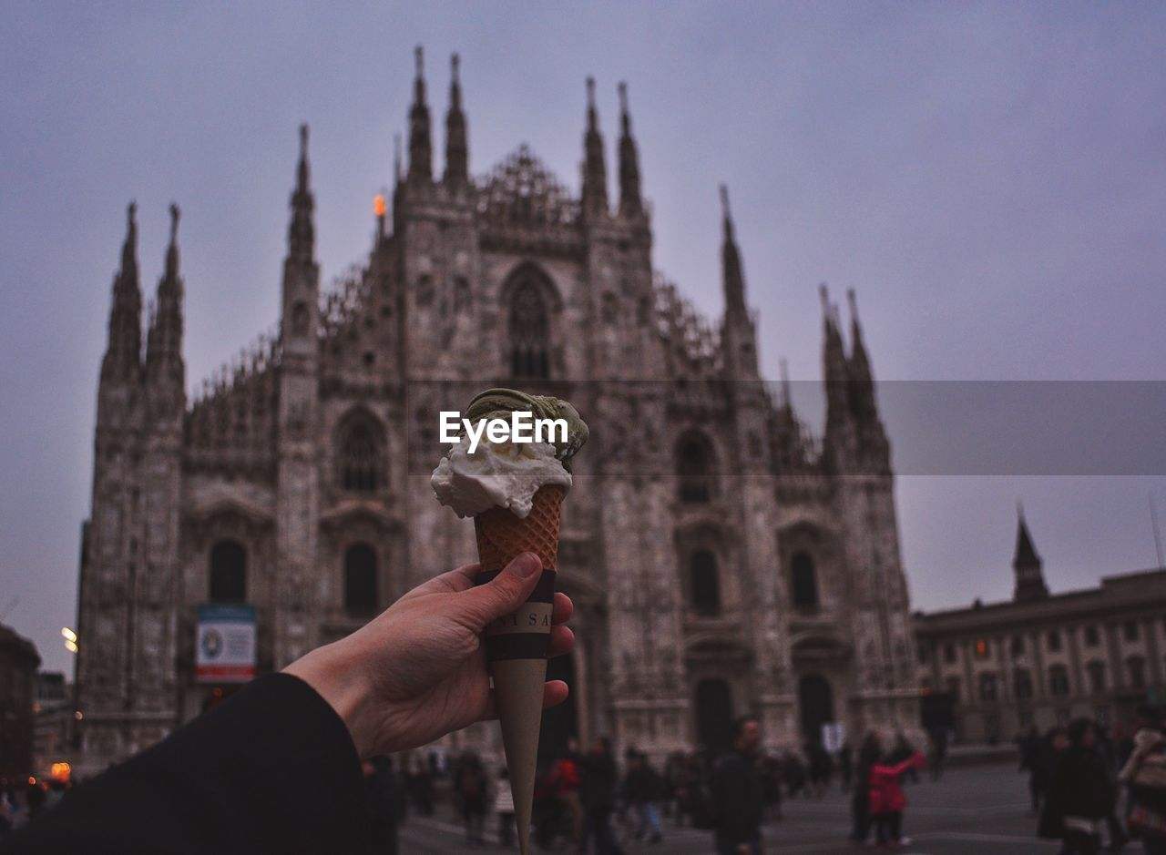Cropped Image Of Hand Holding Ice Cream Cone Against Duomo Di Milano