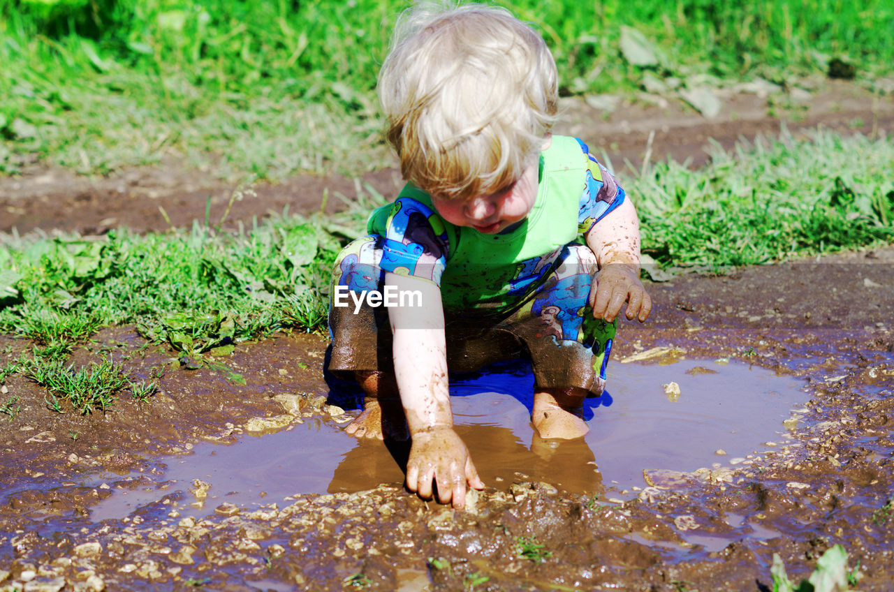 Boy Playing In Muddy Puddle