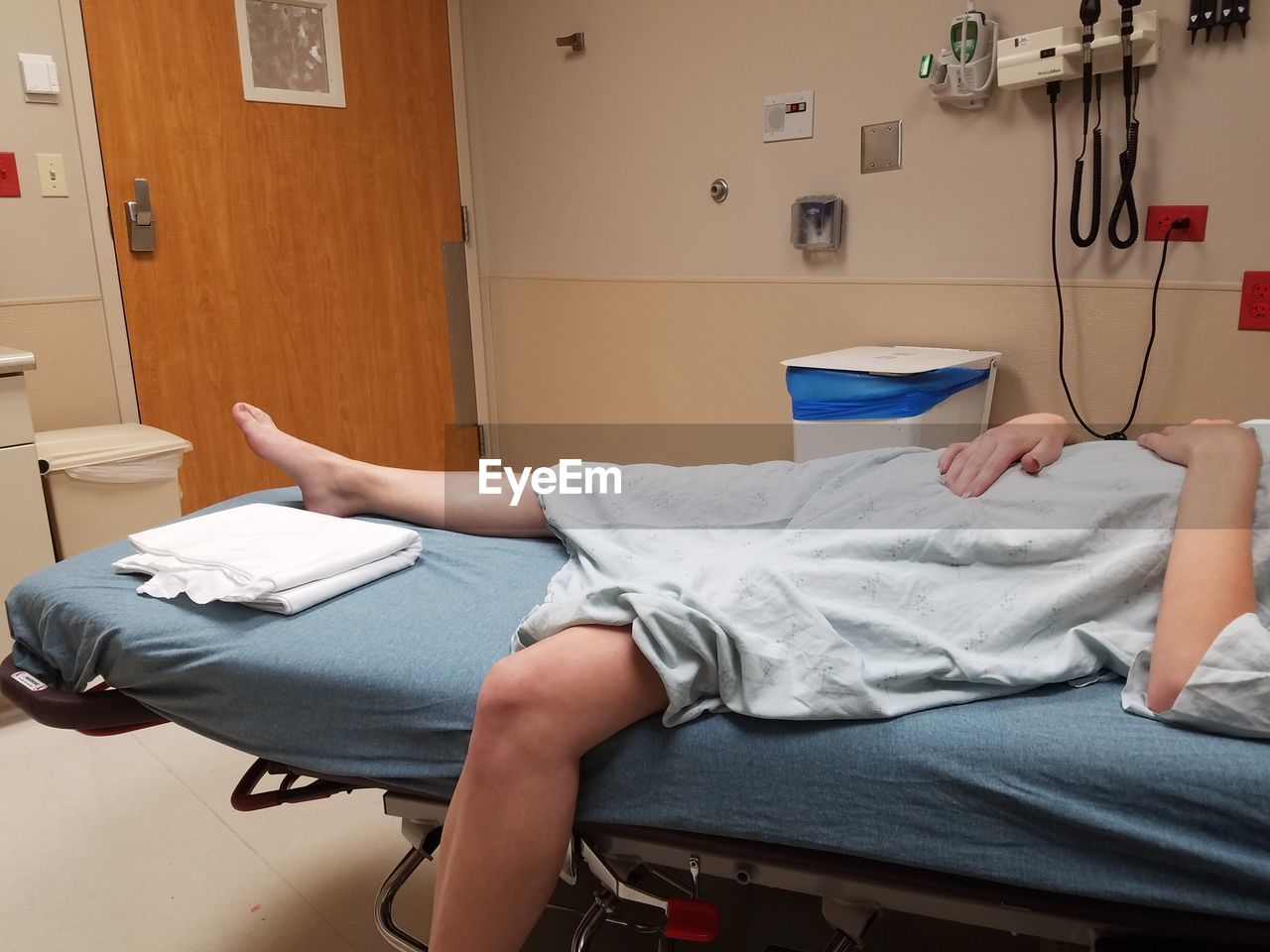 Low Section Of Woman Lying On Hospital Bed
