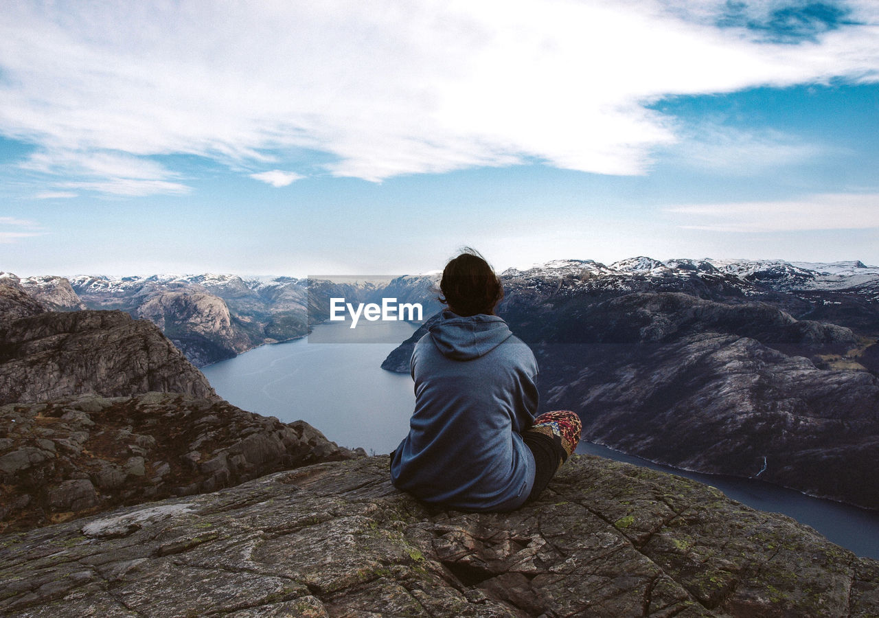 Rear View Of Woman Sitting On Rock While Looking At Fjord Amidst Rocky Mountains Against Sky