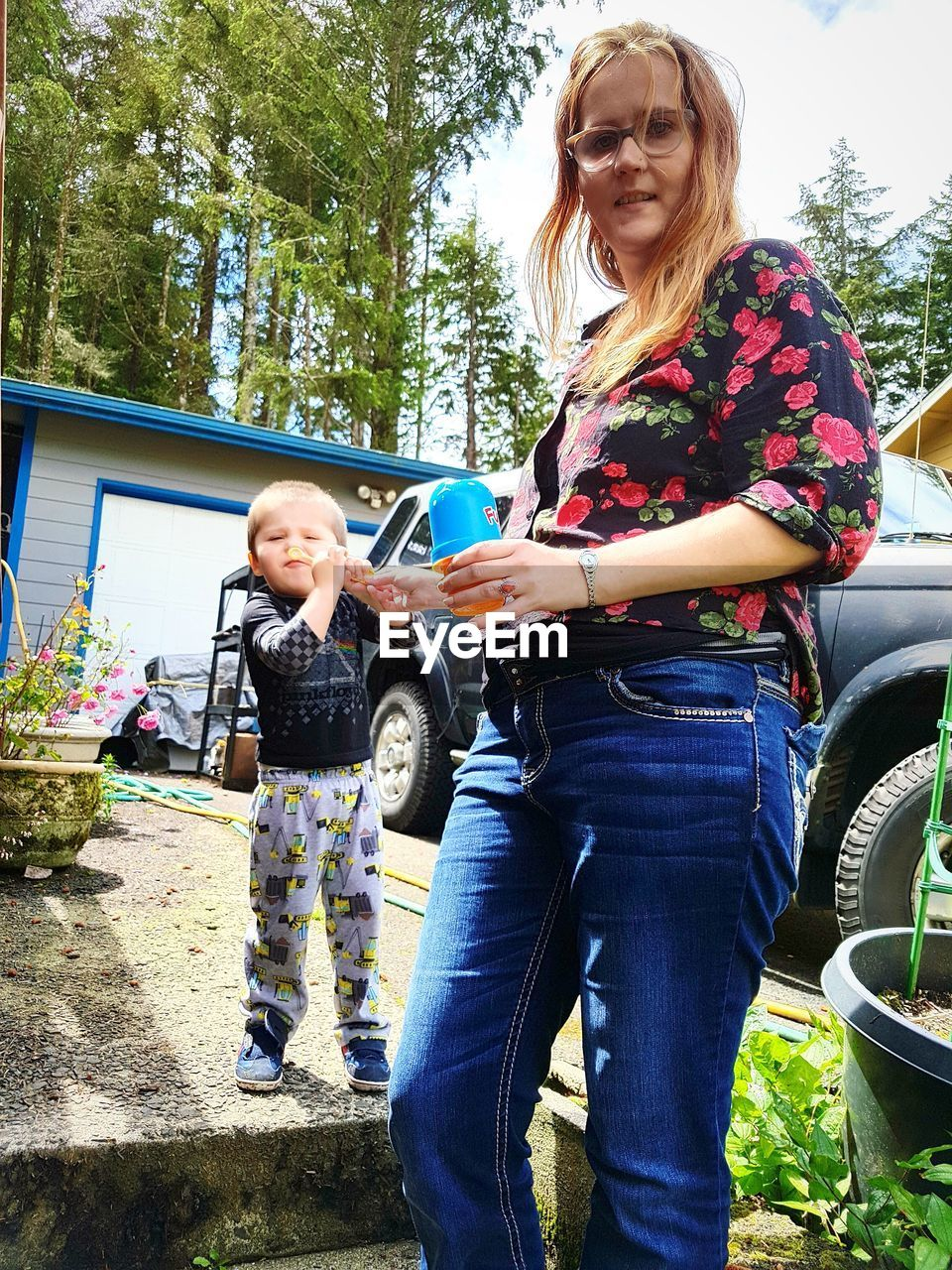 Low angle portrait of mother with son standing in yard