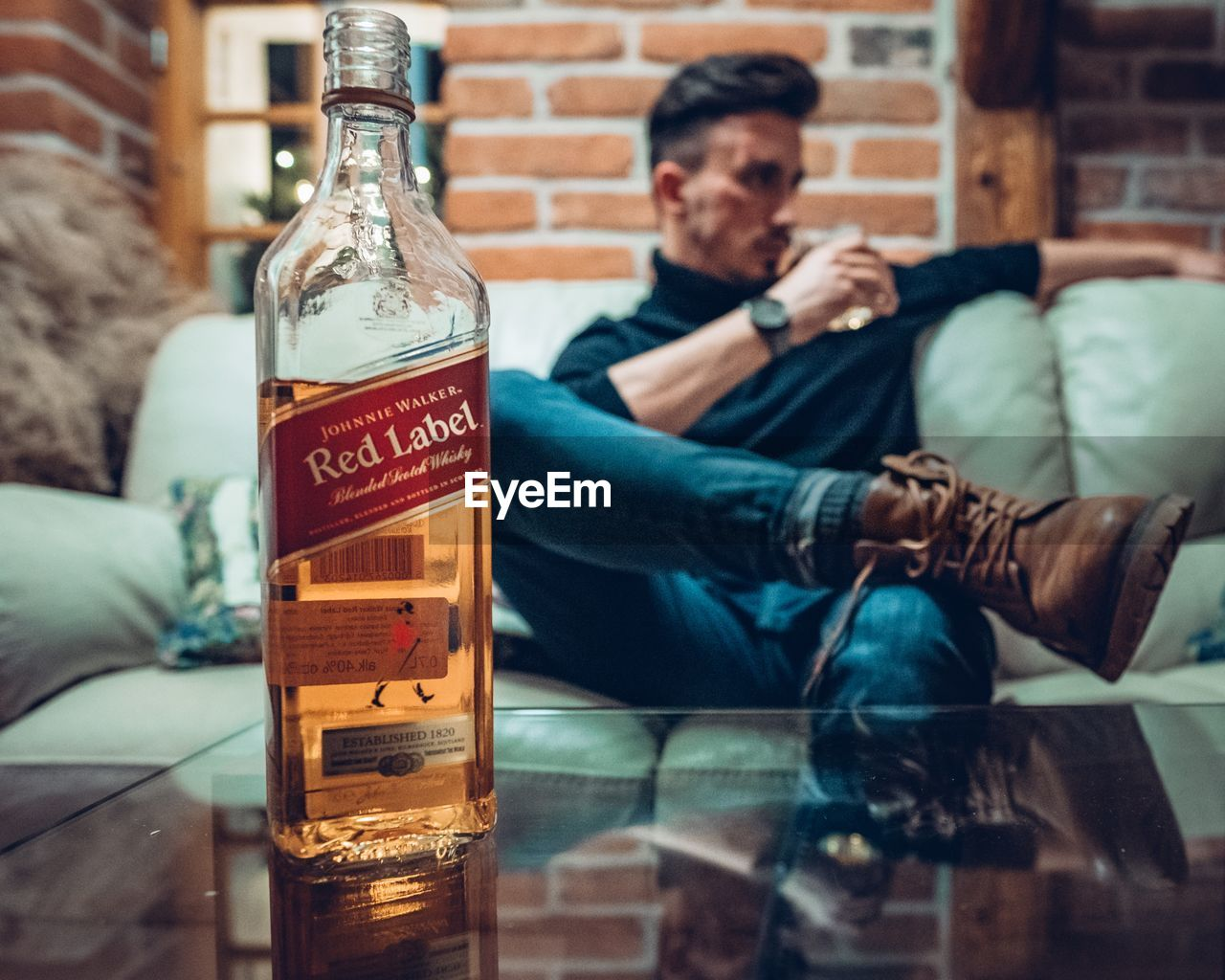 container, casual clothing, bottle, indoors, text, sitting, relaxation, sofa, real people, alcohol, men, food and drink, drink, one person, lifestyles, communication, refreshment, furniture, western script, jeans, glass