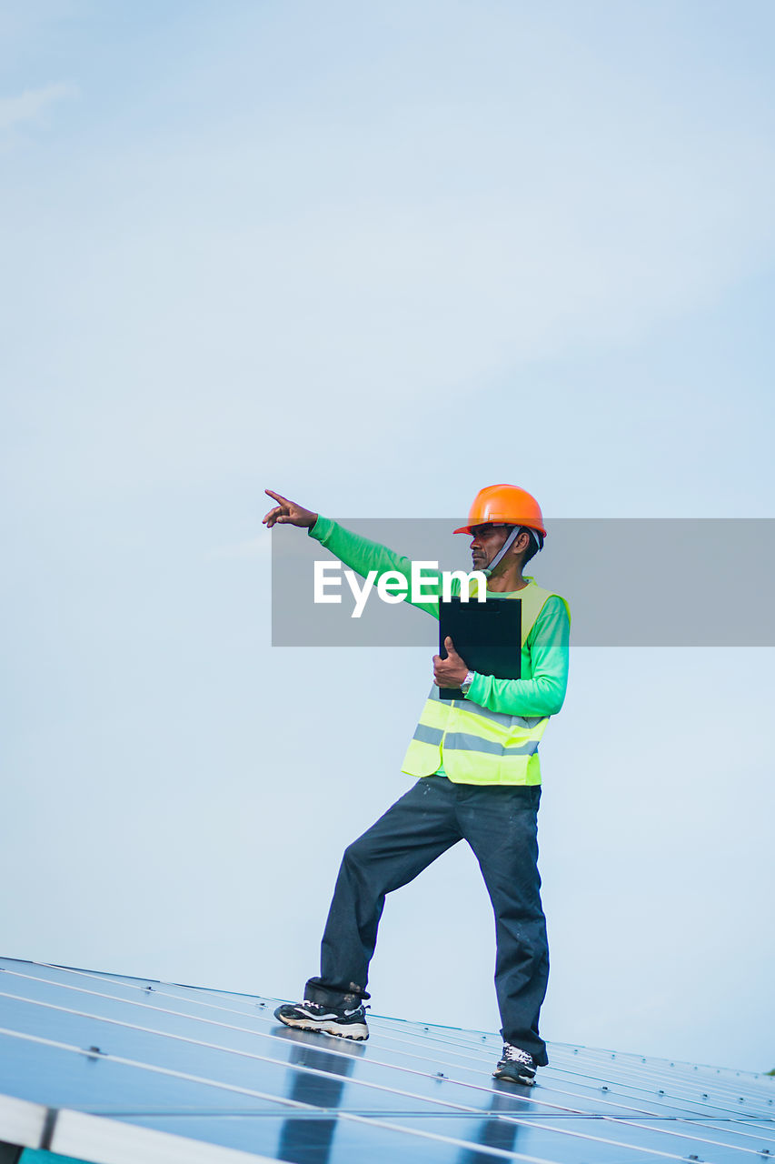 sky, one person, real people, full length, men, day, copy space, standing, nature, casual clothing, holding, occupation, helmet, lifestyles, headwear, low angle view, hardhat, clothing, human arm, outdoors, arms raised