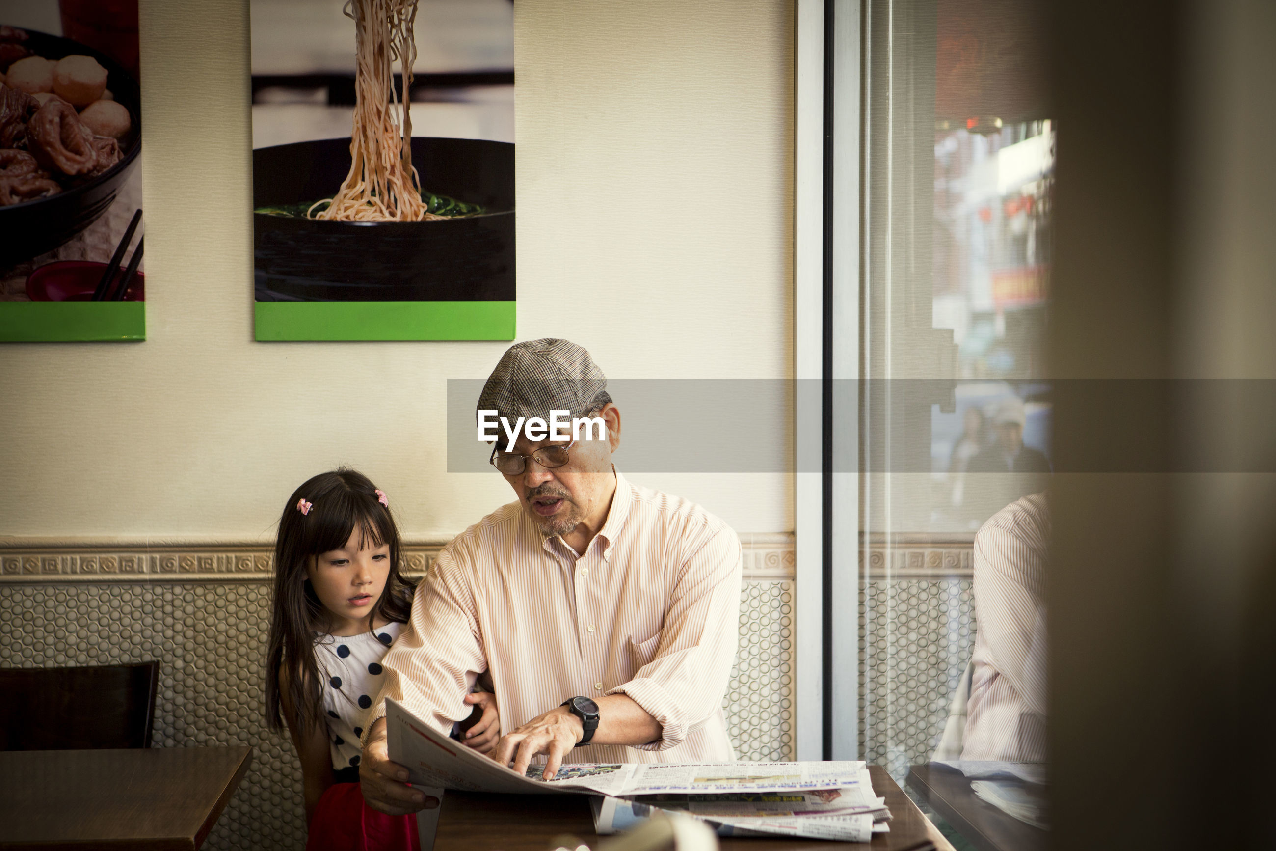 Grandfather showing newspaper while sitting with granddaughter in restaurant