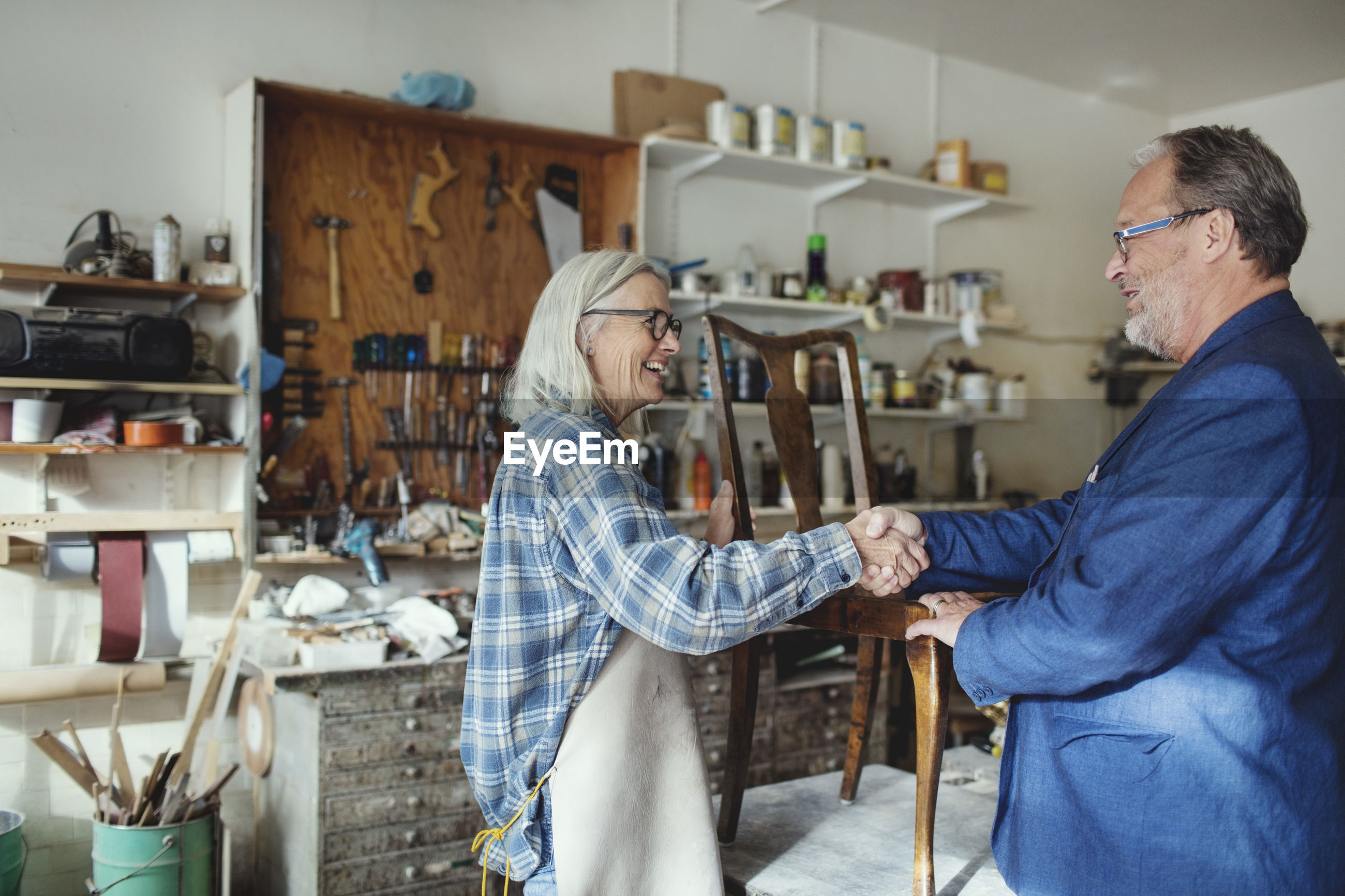 Senior owner shaking hands with customer while selling wooden chair at workshop
