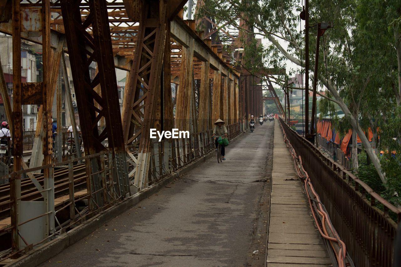 Man on footbridge amidst trees