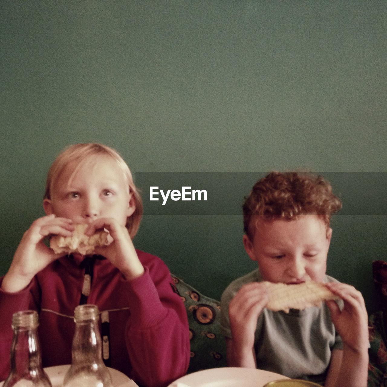 Cute Siblings Eating Food At Home