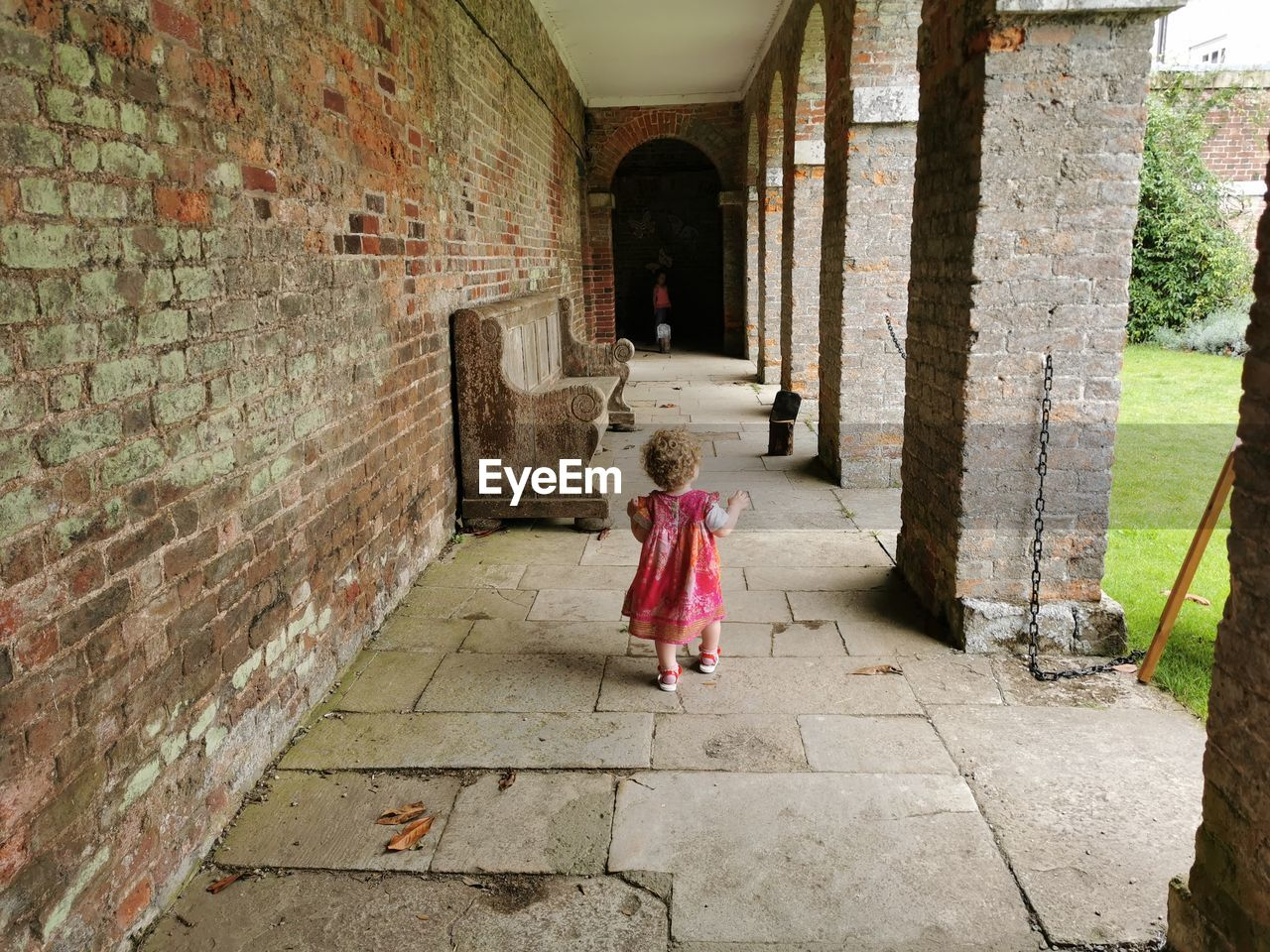 Rear view of girl walking independently though a courtyard