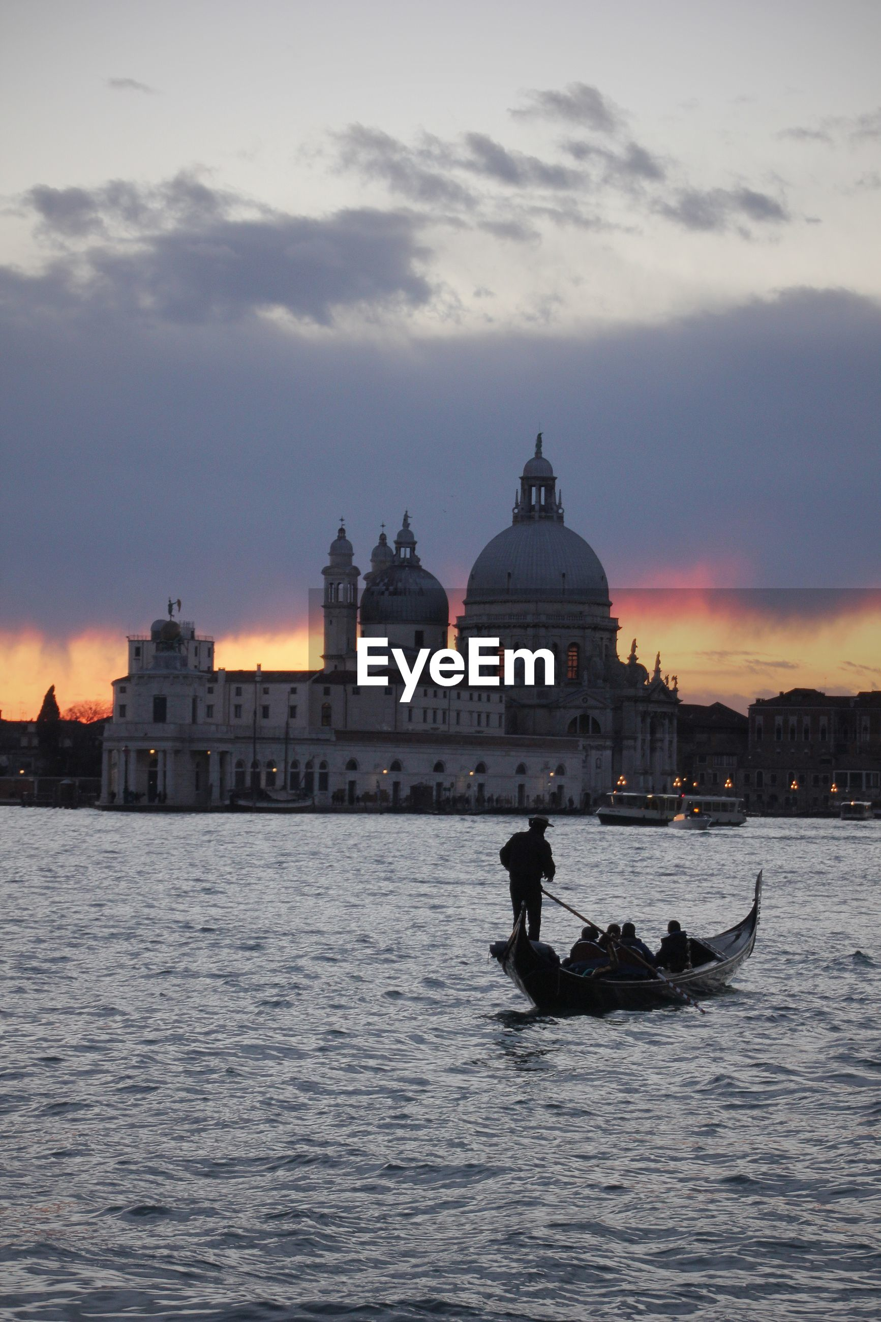 Gondolier in grand canal against santa maria della salute during sunset