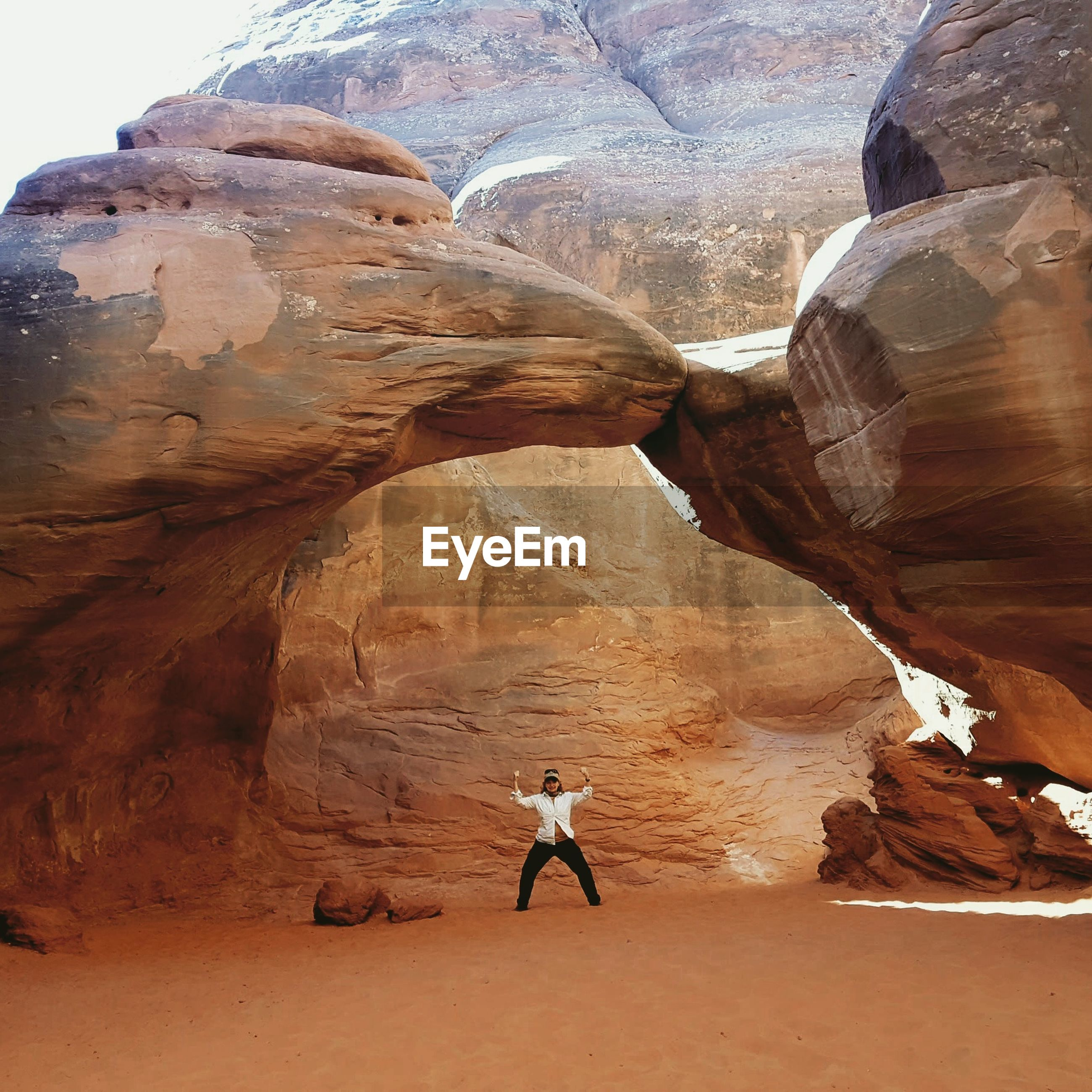 Woman standing under rock formations in desert