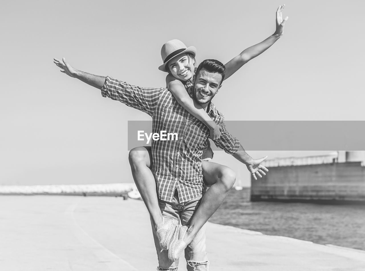 Portrait of smiling young man with girlfriend on back by sea