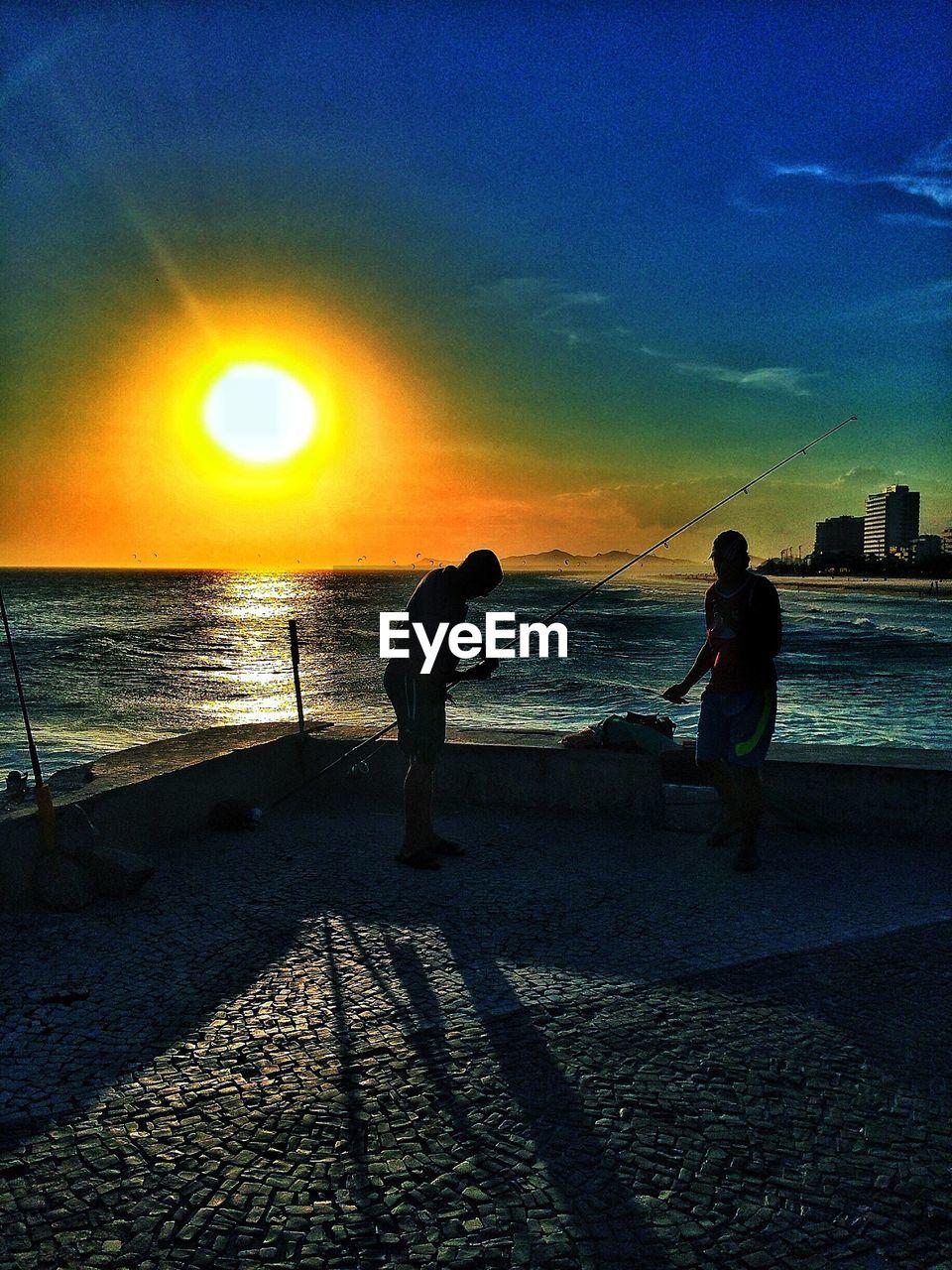 Silhouette men fishing against sea during sunset