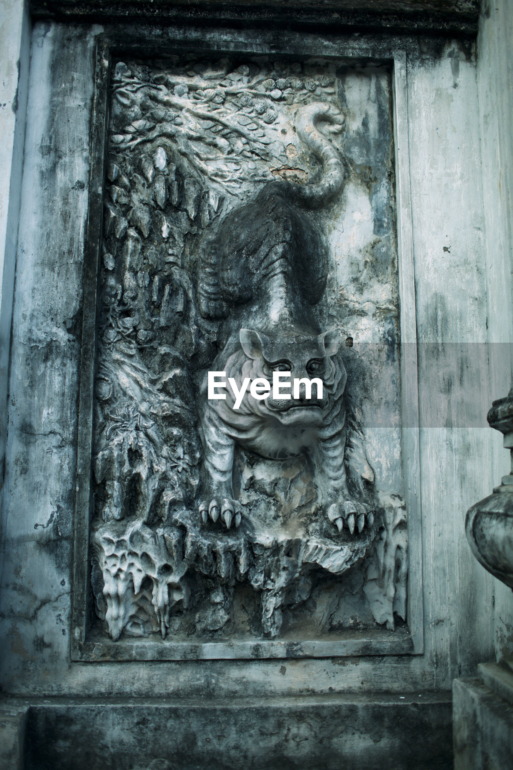 CLOSE-UP OF OLD SCULPTURE AGAINST DOOR OF BUILDING