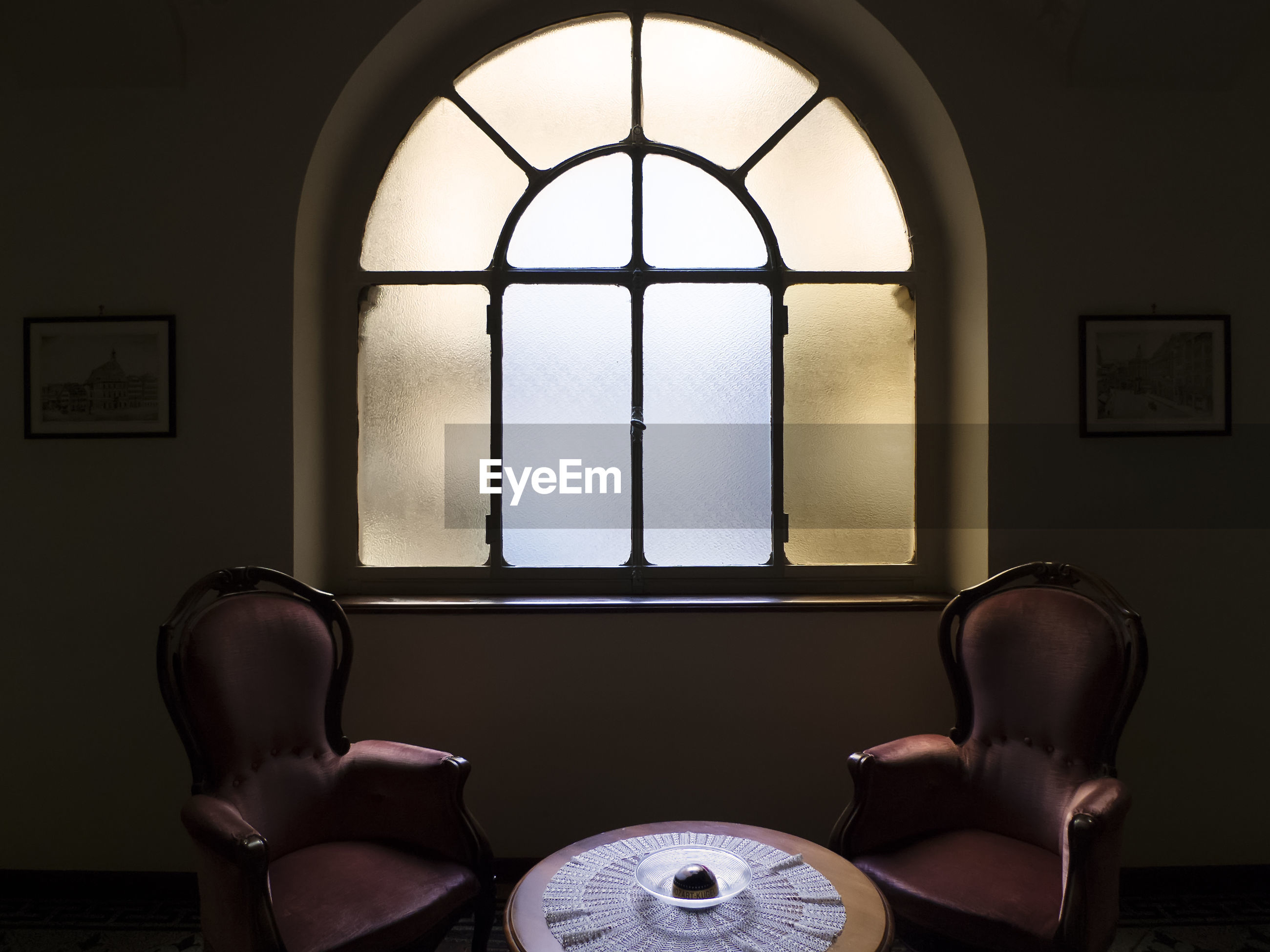 EMPTY CHAIR AND TABLE IN WINDOW