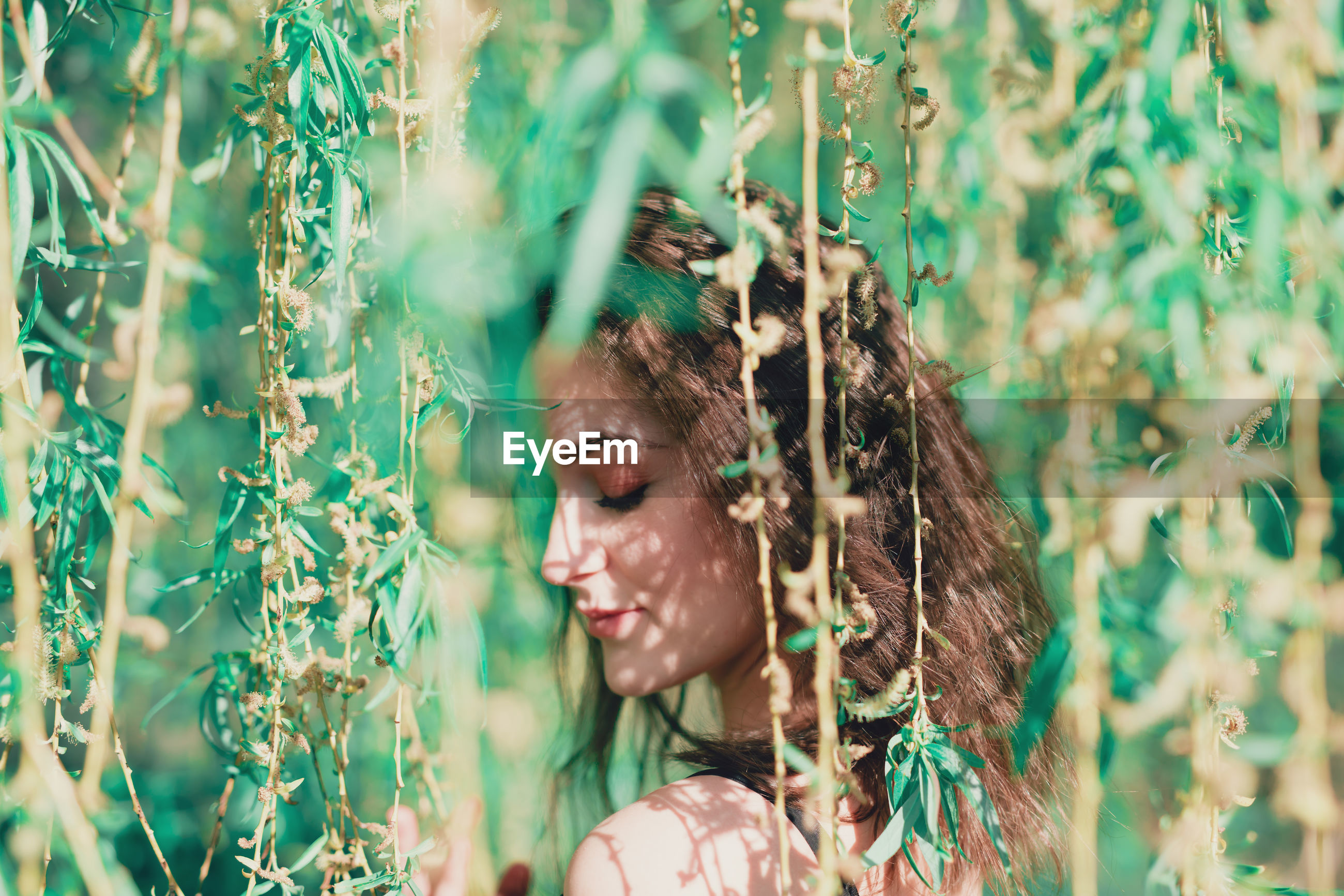 Side view of woman with eyes closed standing by plants in park