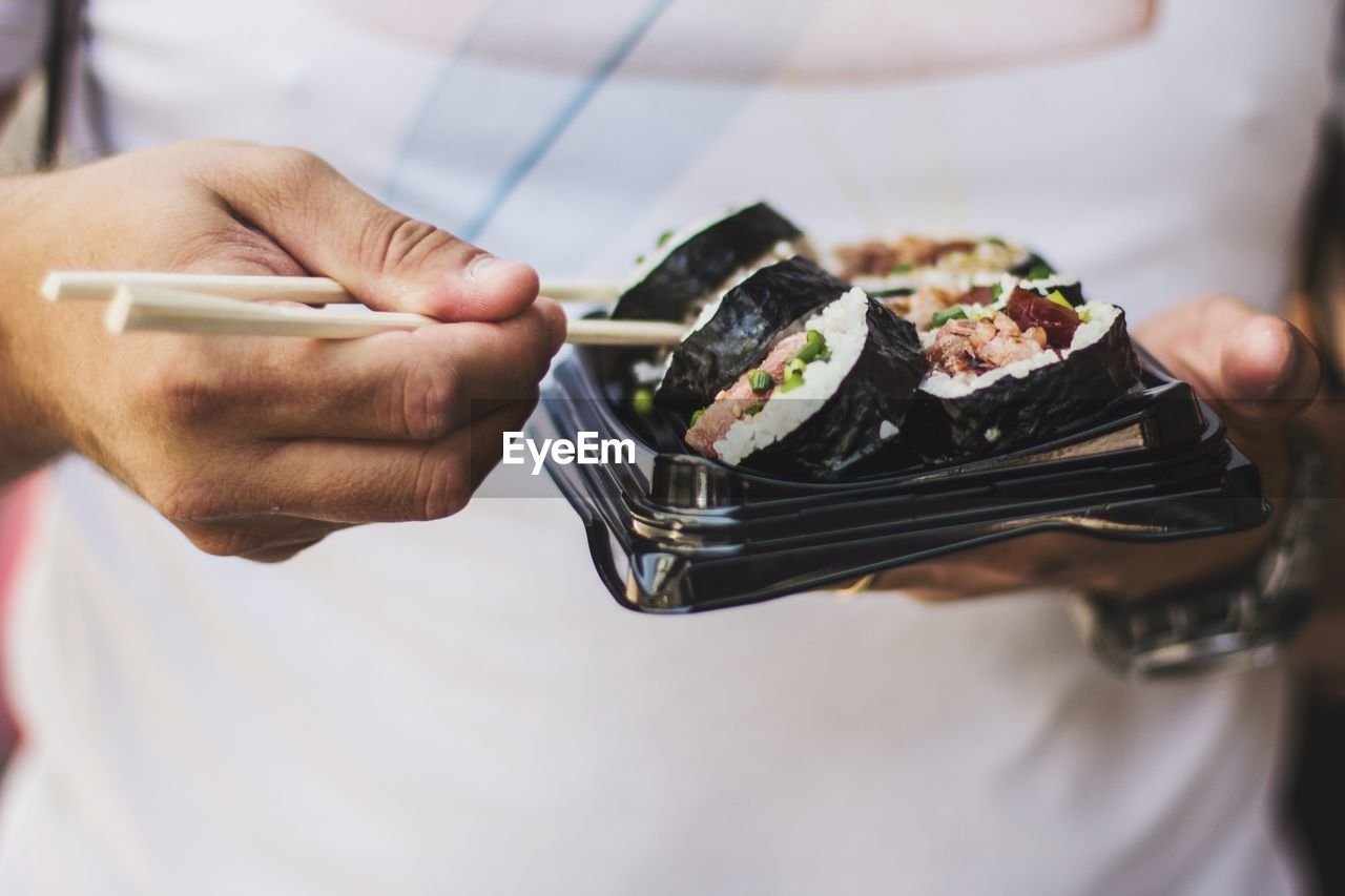 Midsection Of Man With Sushi Holding In Container