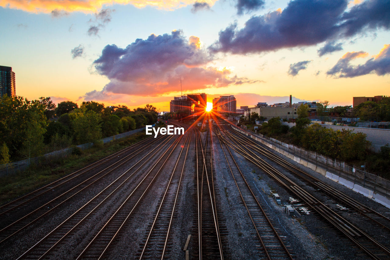 sunset, sky, track, cloud - sky, rail transportation, railroad track, transportation, nature, no people, orange color, sunlight, tree, direction, the way forward, sun, architecture, plant, building exterior, beauty in nature, outdoors, lens flare
