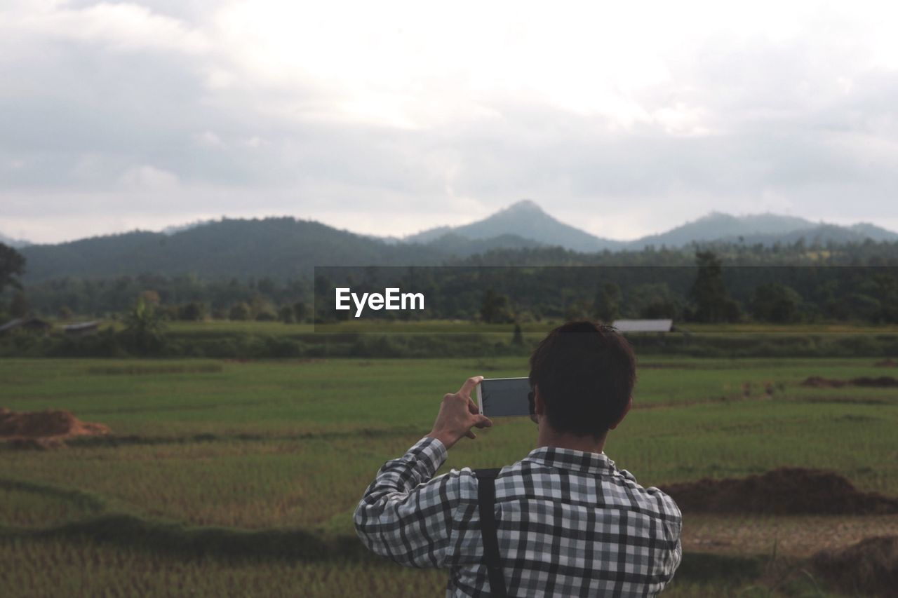 Man photographing landscape view through smart phone