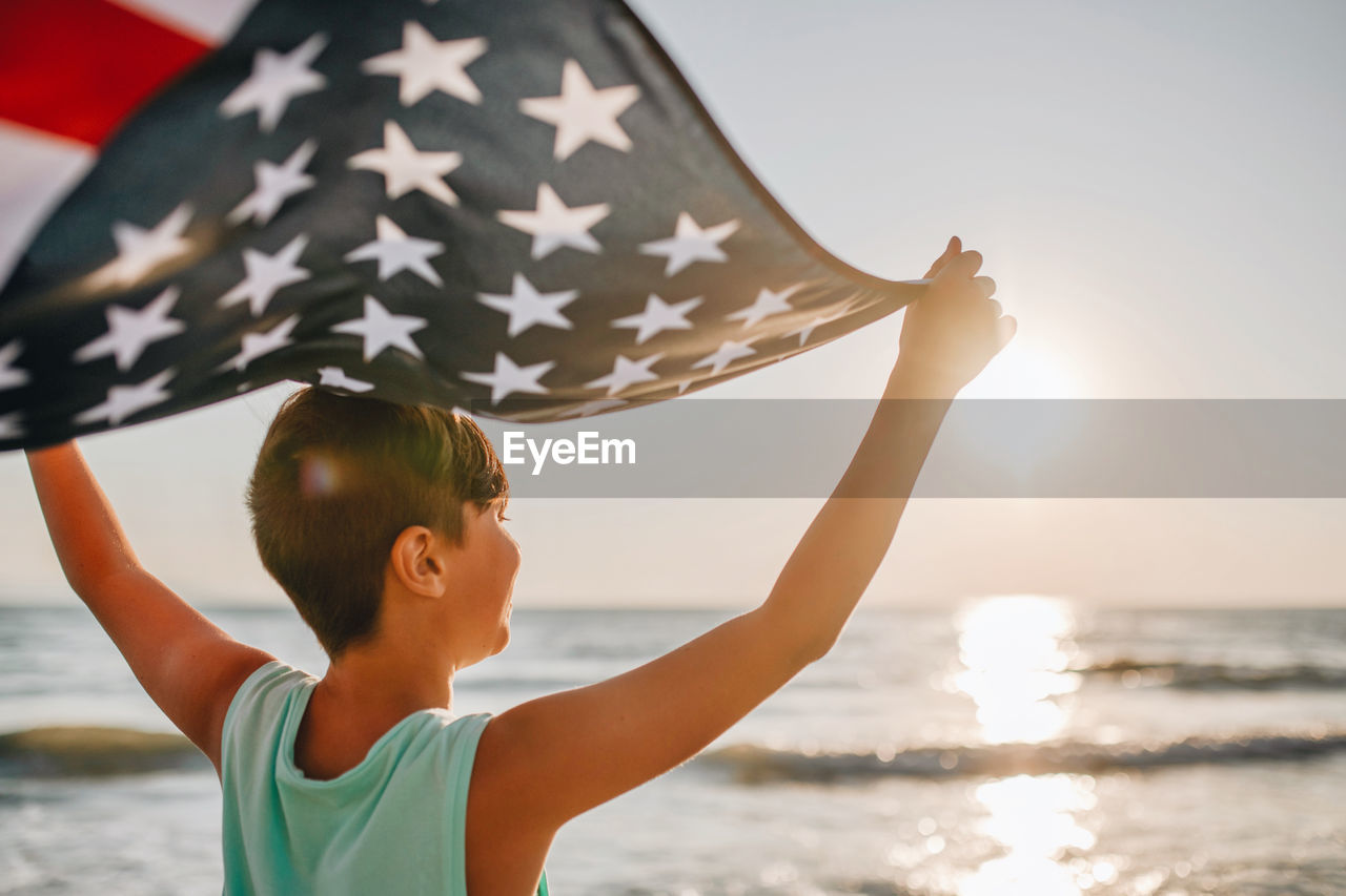 Boy holding american flag at beach during sunset