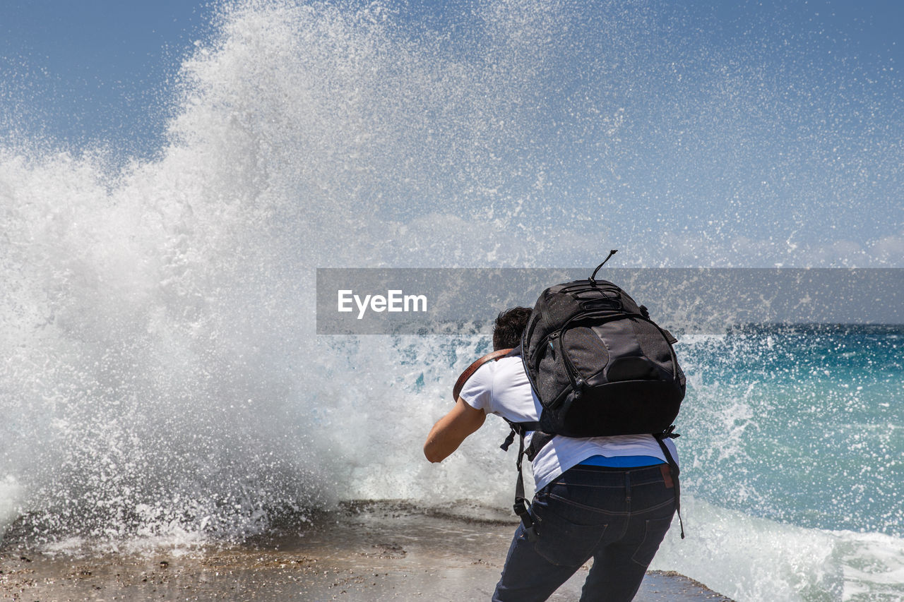 Man photographing wave