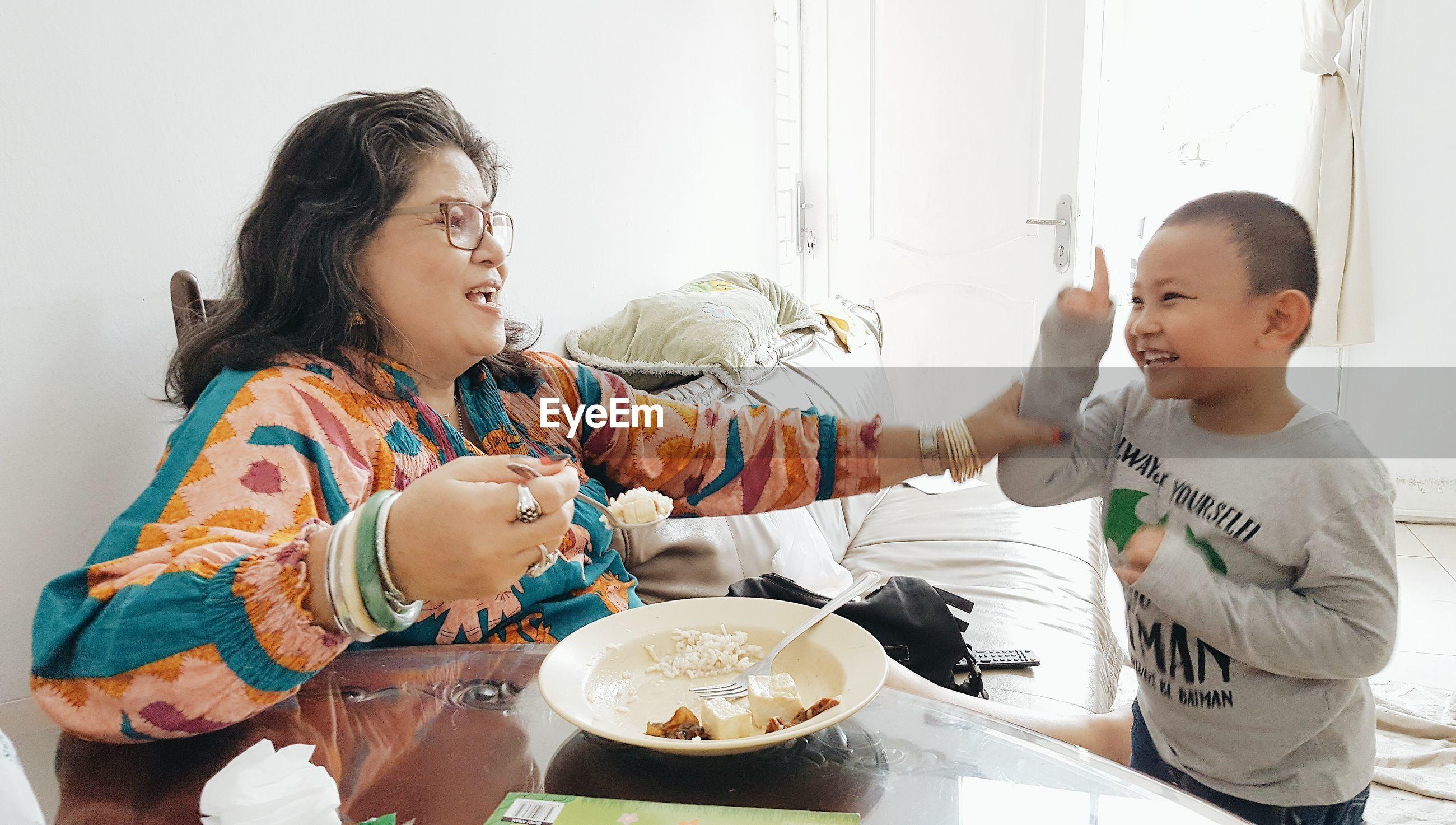 Woman feeding cheerful son at home