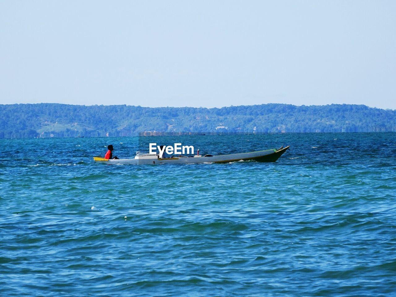 Fishermen In Boat On Sea Against Clear Sky