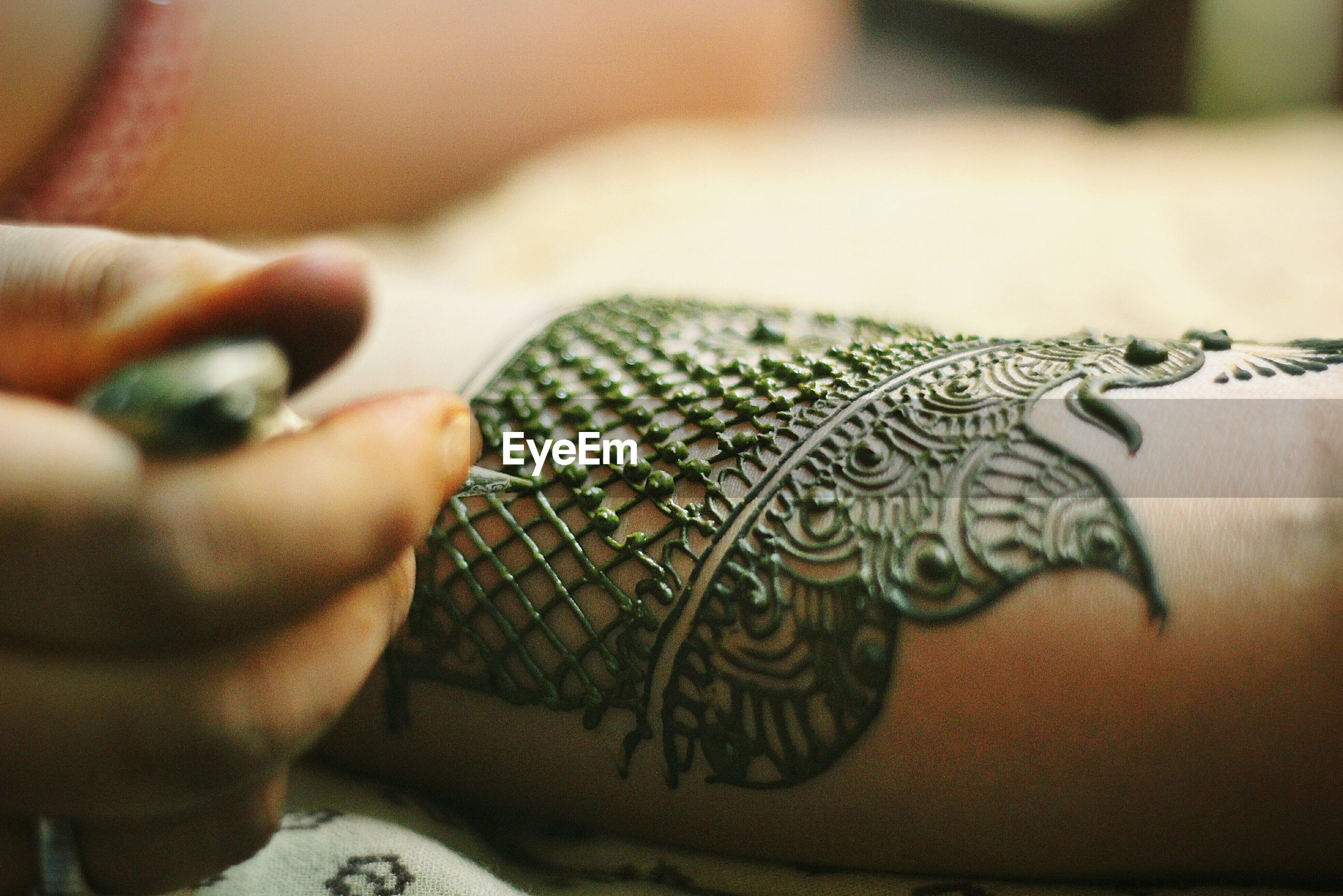 Artist drawing henna tattoo on cropped hand of bride