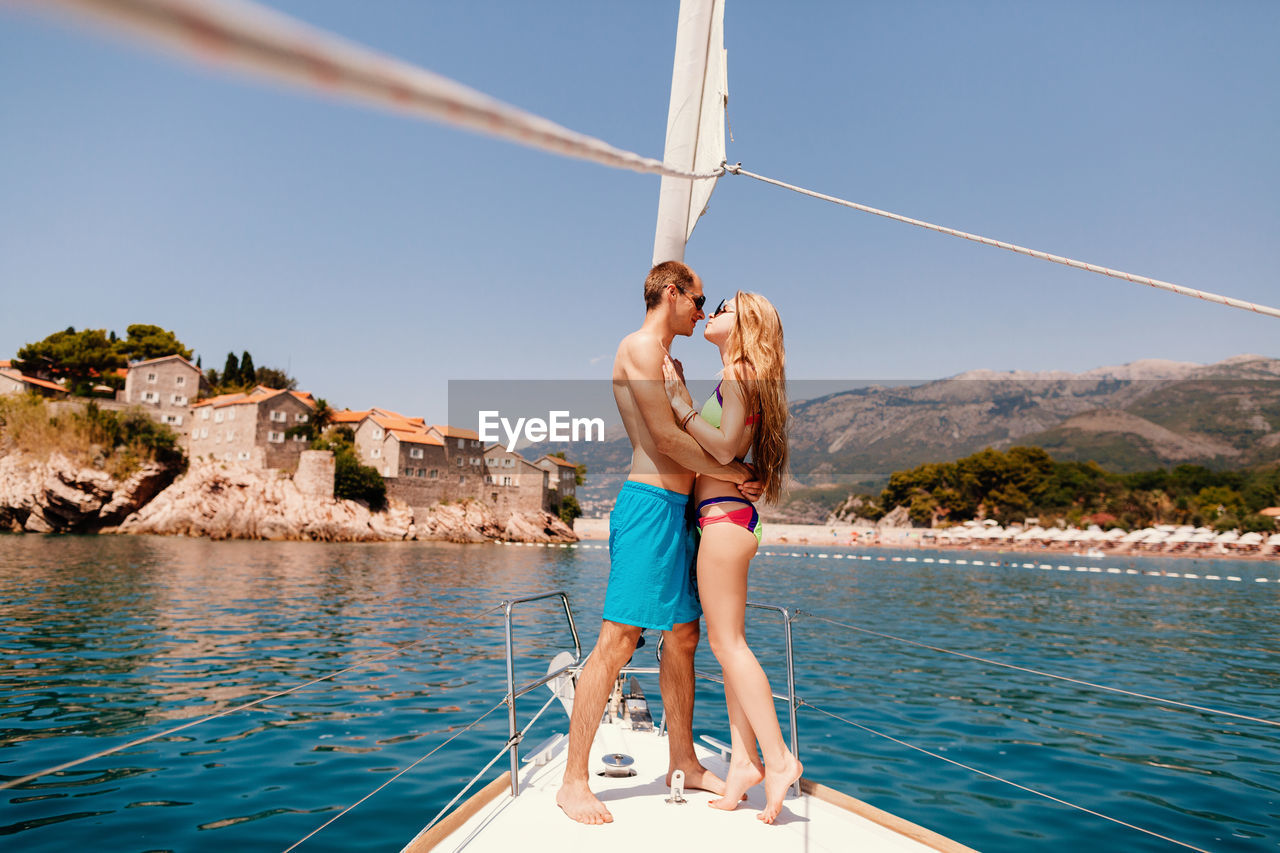 Side View Of Couple Romancing On Yacht Sailing In Sea