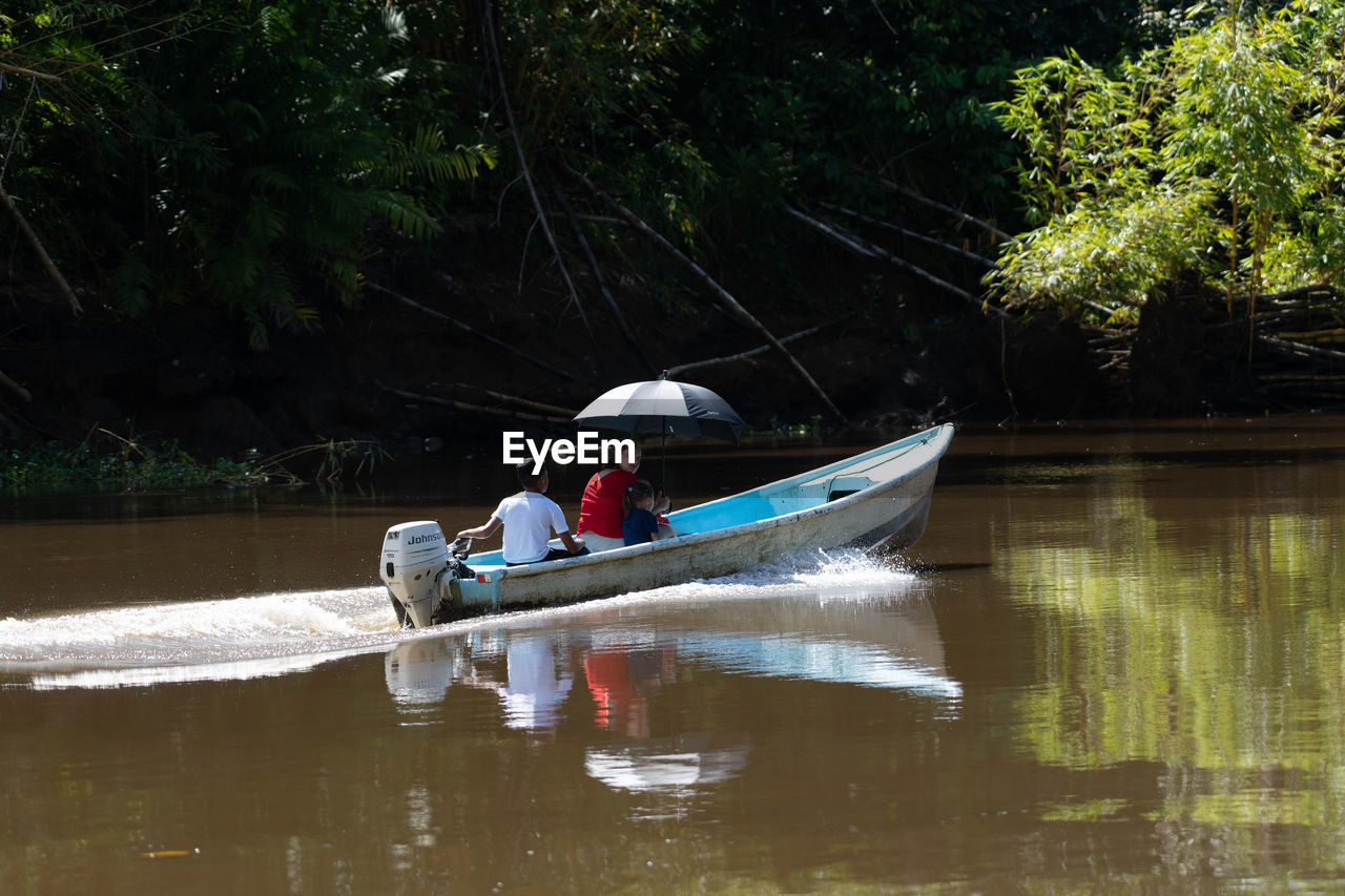PEOPLE ON BOAT IN LAKE