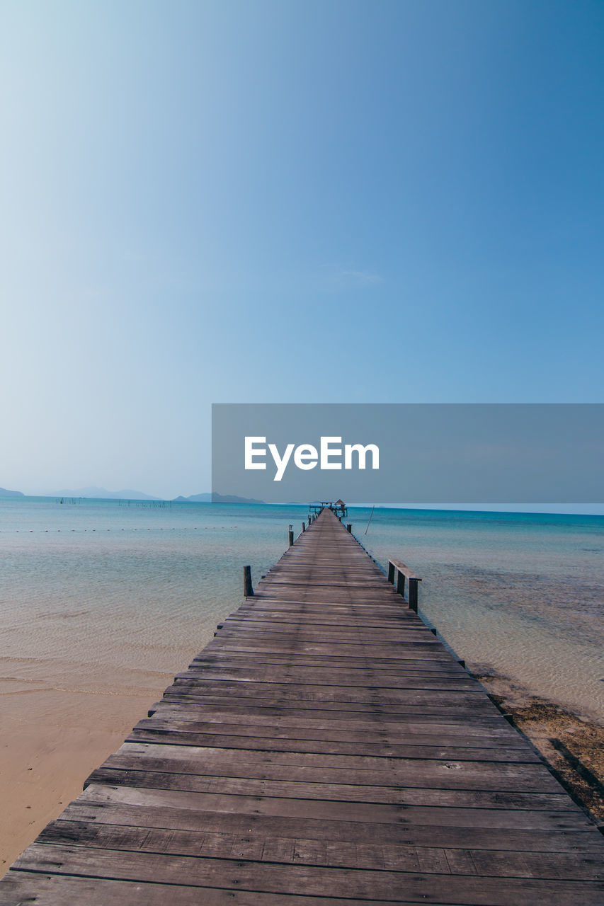sky, horizon, direction, sea, the way forward, water, horizon over water, scenics - nature, beauty in nature, tranquil scene, tranquility, land, beach, wood - material, diminishing perspective, nature, pier, clear sky, idyllic, no people, wood, outdoors, wood paneling, long, wooden post