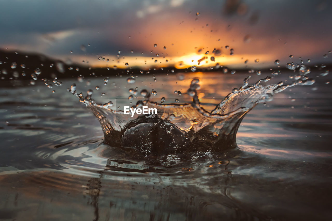 Close-Up Of Water Splashing Against Sky During Sunset