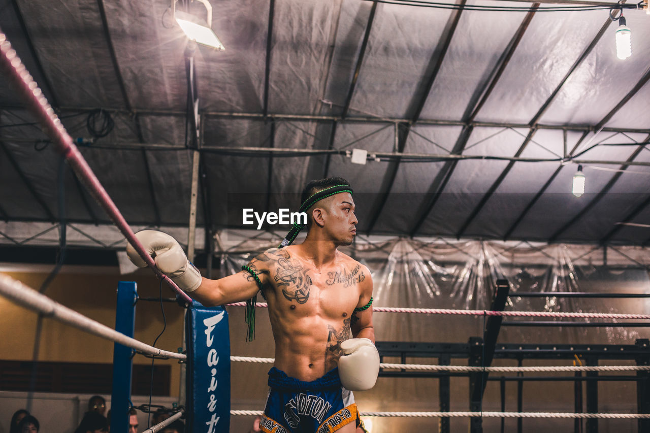 one person, real people, front view, lifestyles, indoors, standing, shirtless, lighting equipment, three quarter length, young adult, holding, young men, illuminated, sport, leisure activity, healthy lifestyle, determination, exercising, ceiling
