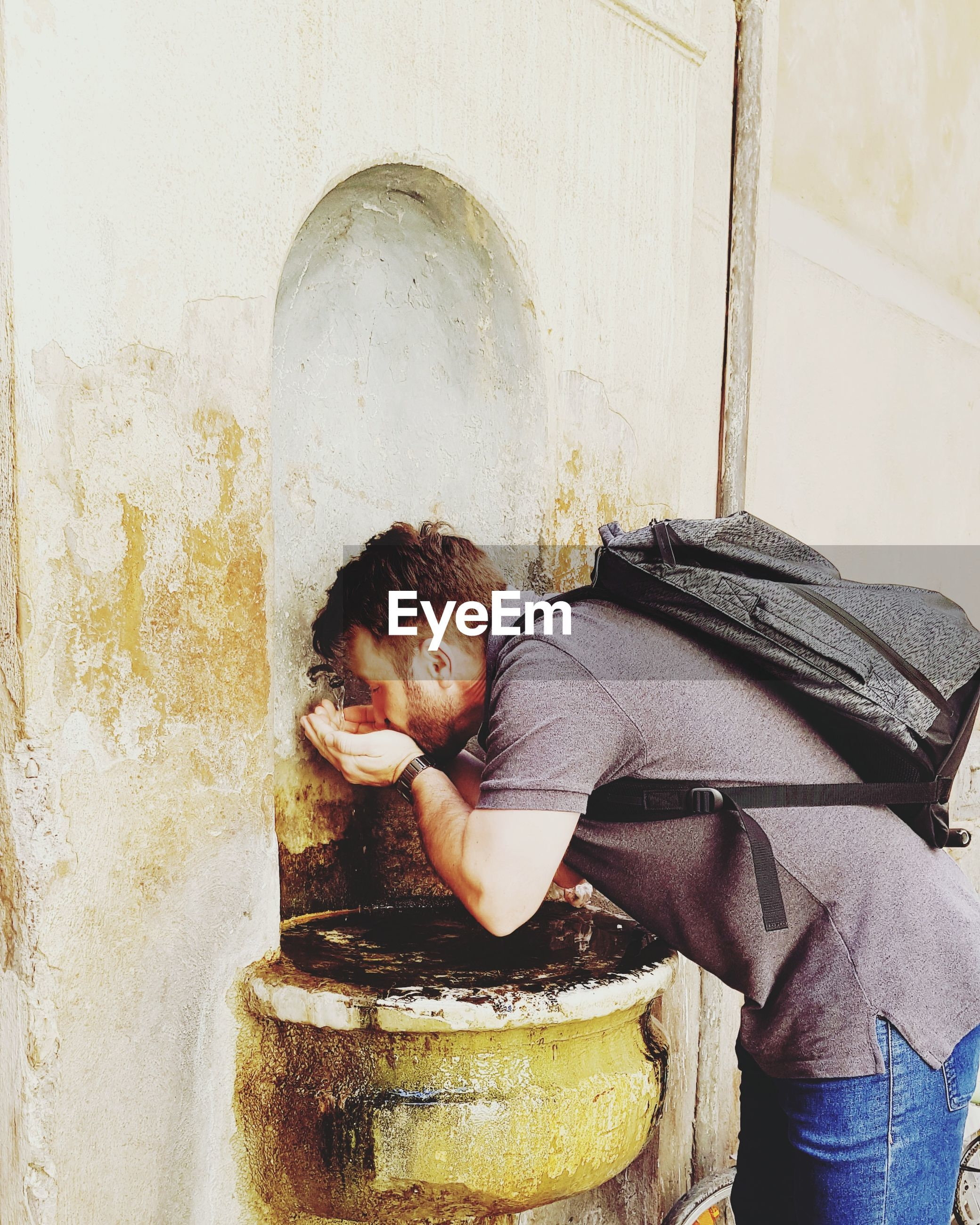 Man drinking water from tap