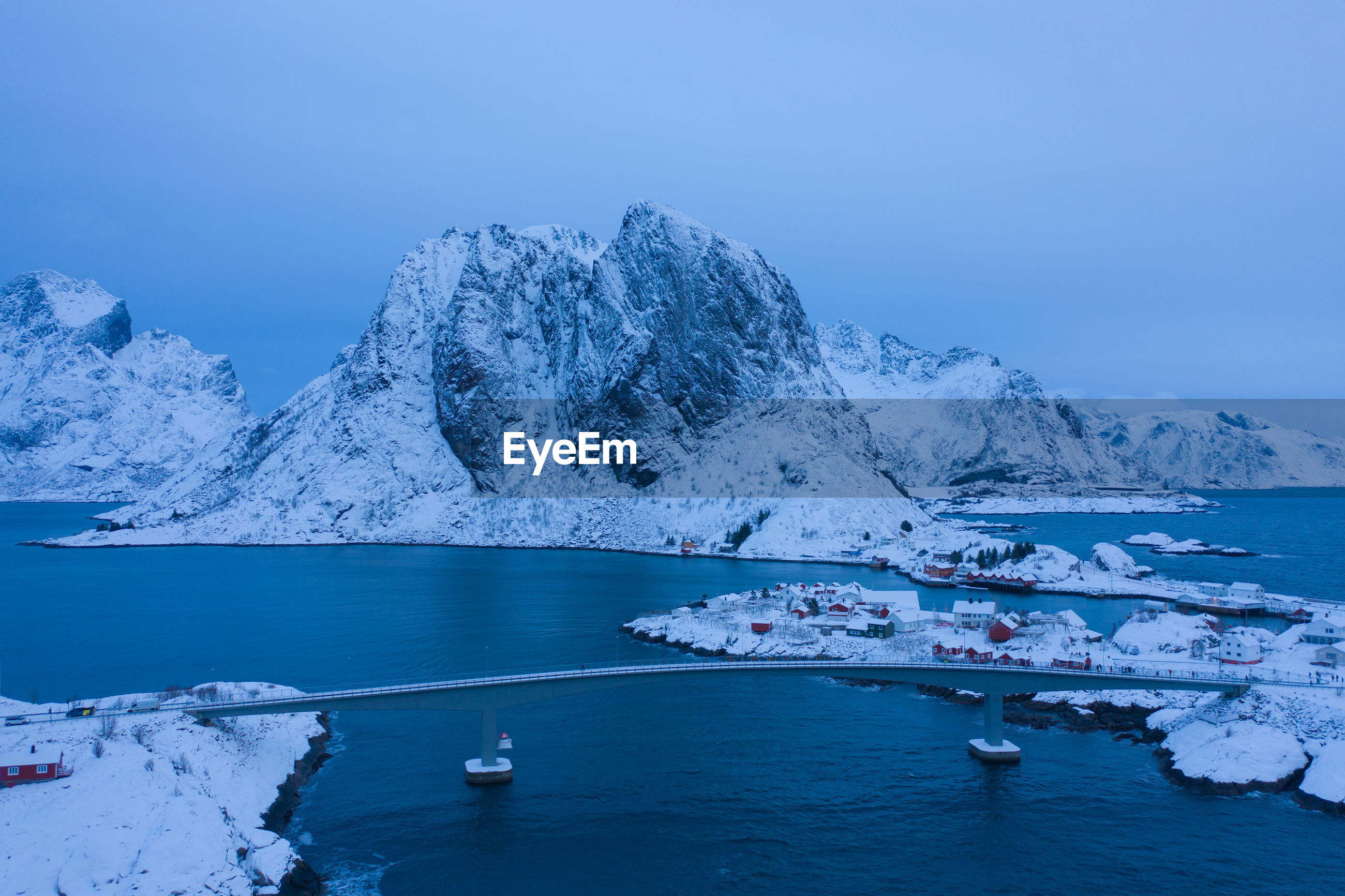SCENIC VIEW OF SEA BY SNOWCAPPED MOUNTAIN AGAINST BLUE SKY