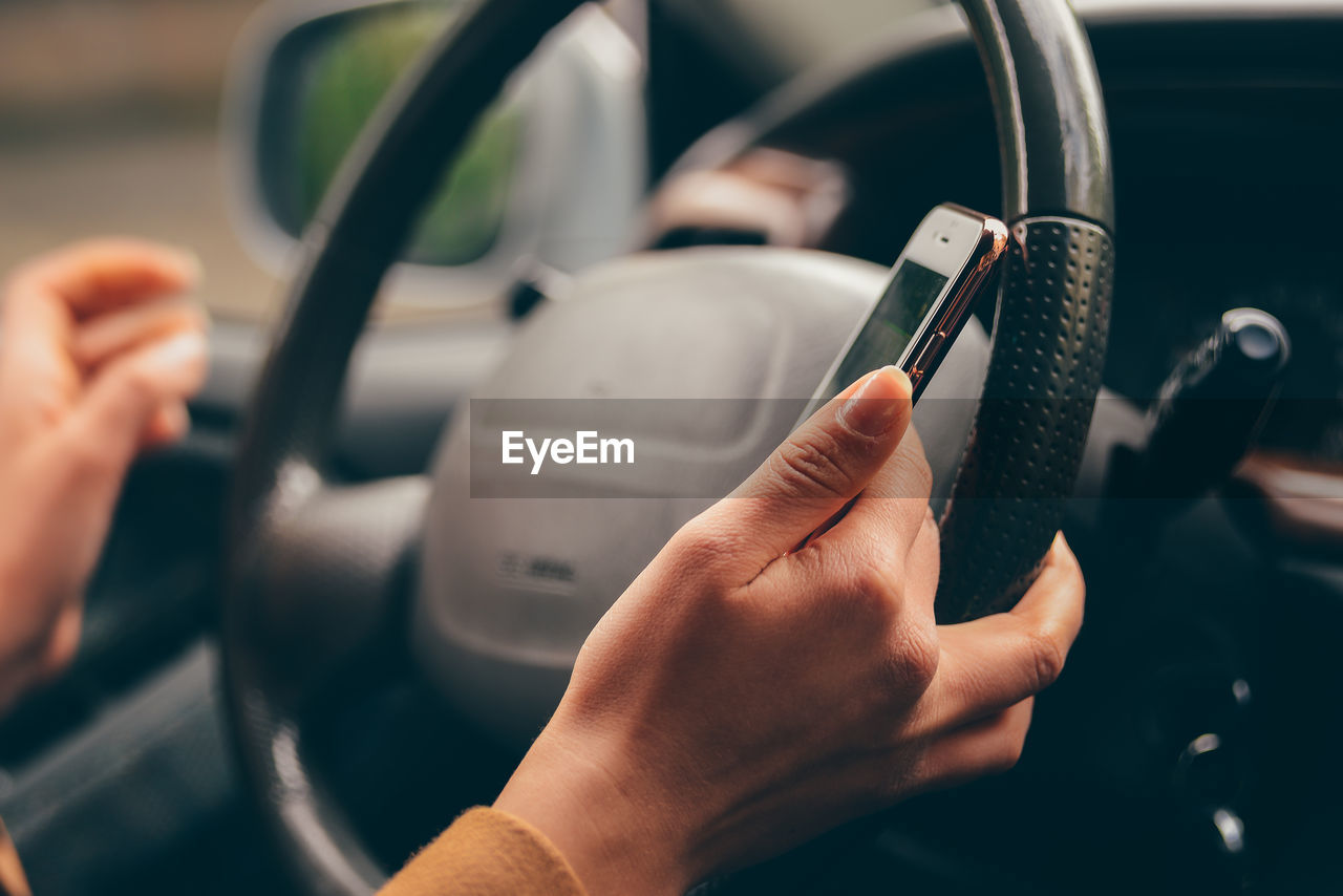Cropped hands of woman using mobile phone while driving car