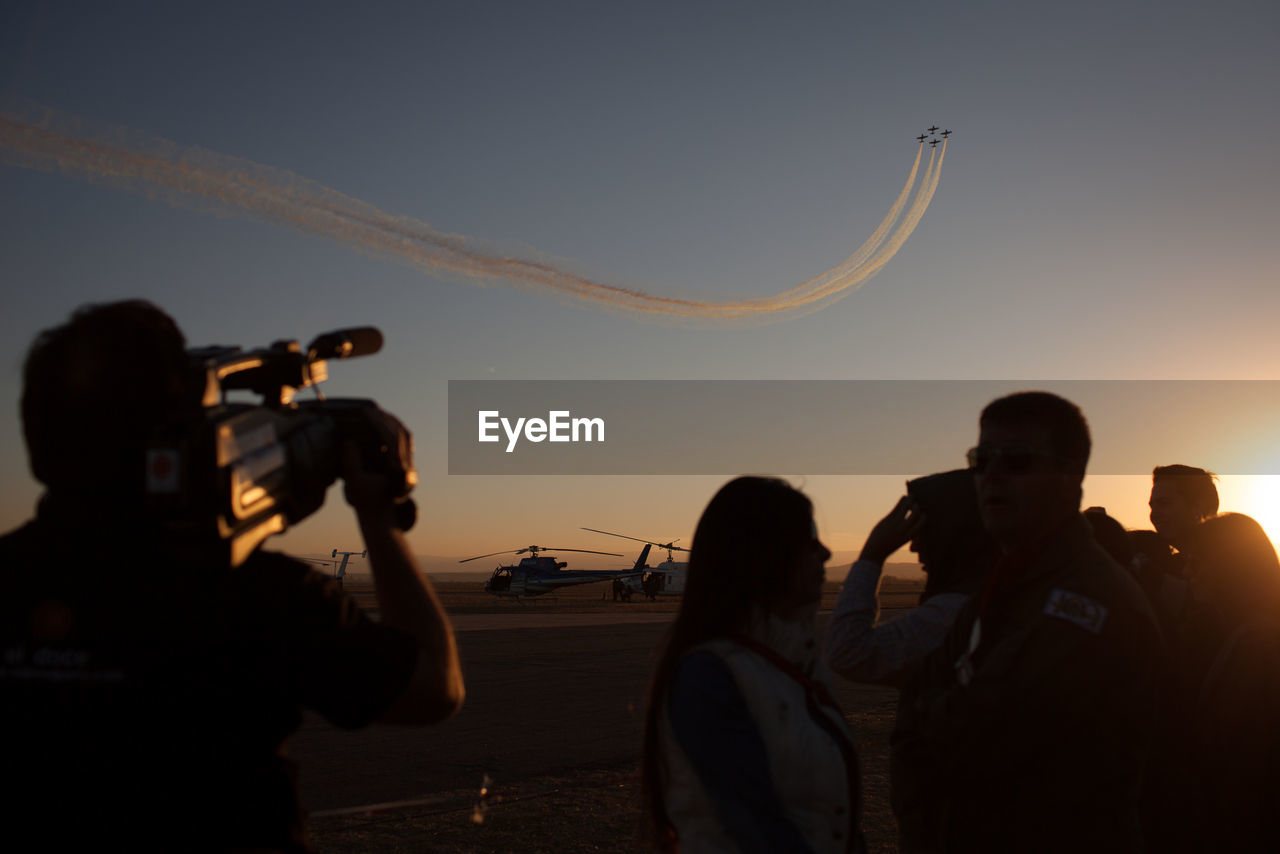 Rear View Of Man Photographing Airshow During Sunset