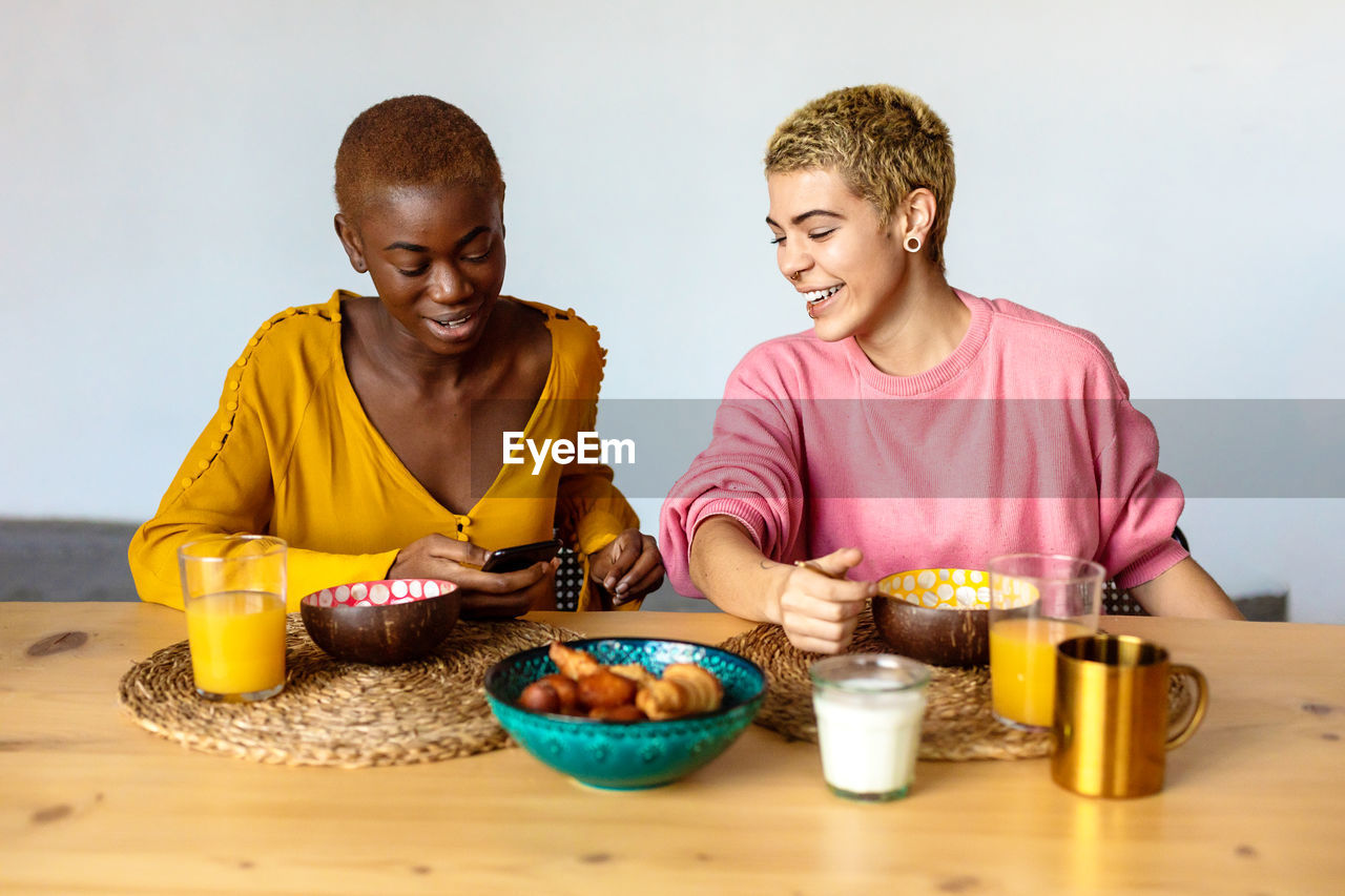 TWO PEOPLE SITTING ON TABLE