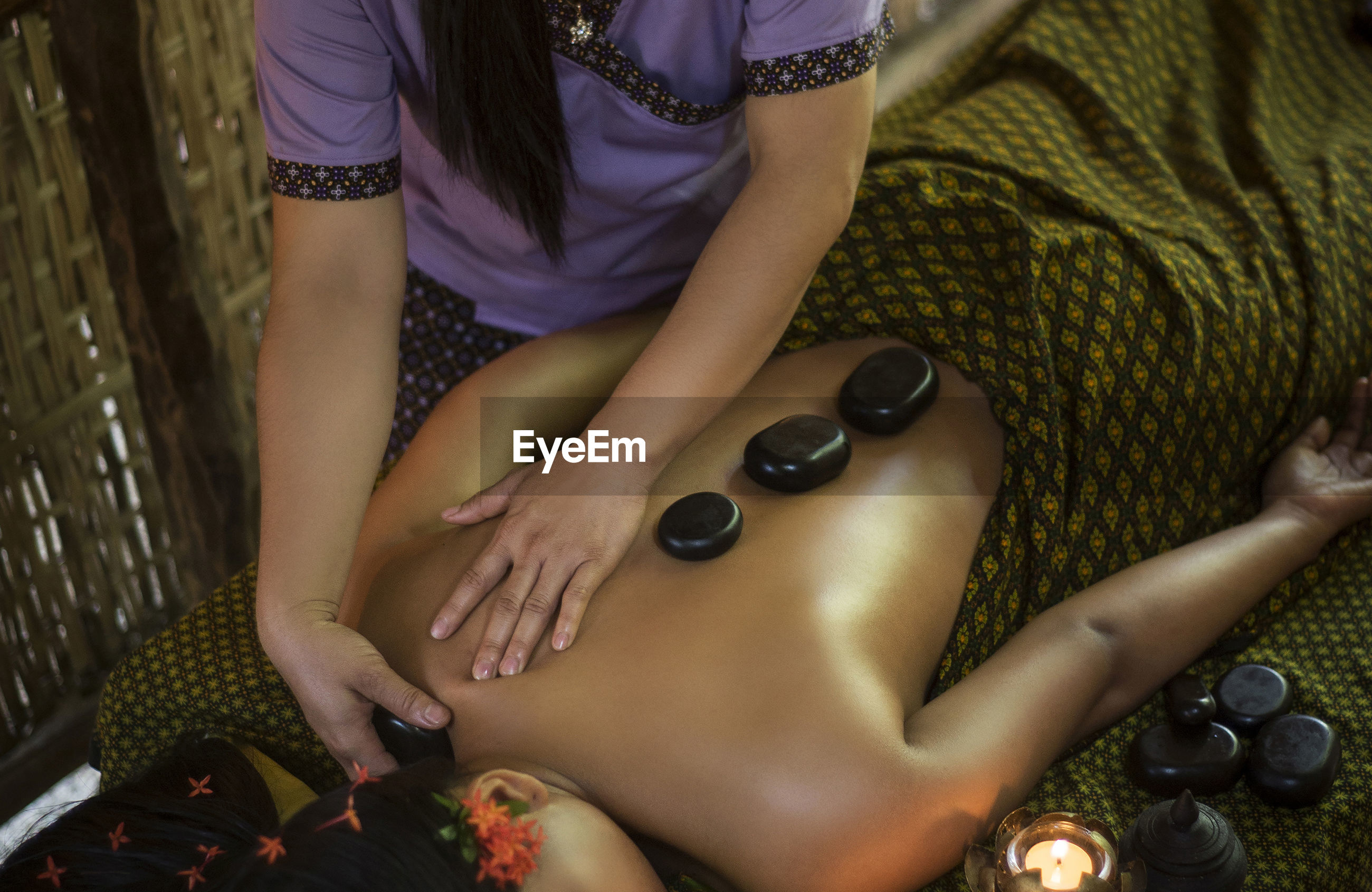 Midsection of woman getting herbal message at spa