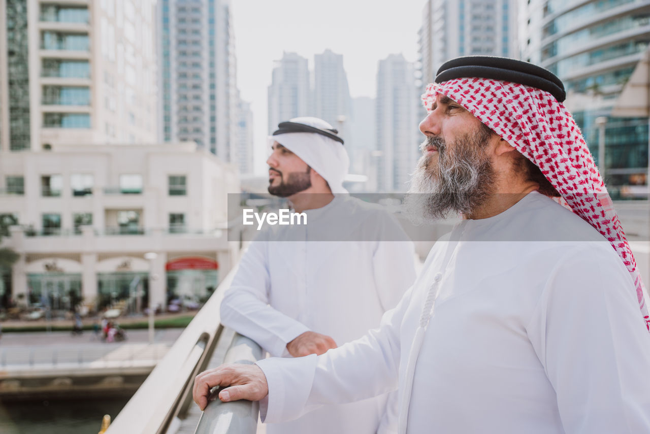 Men in traditional clothing looking away outdoors