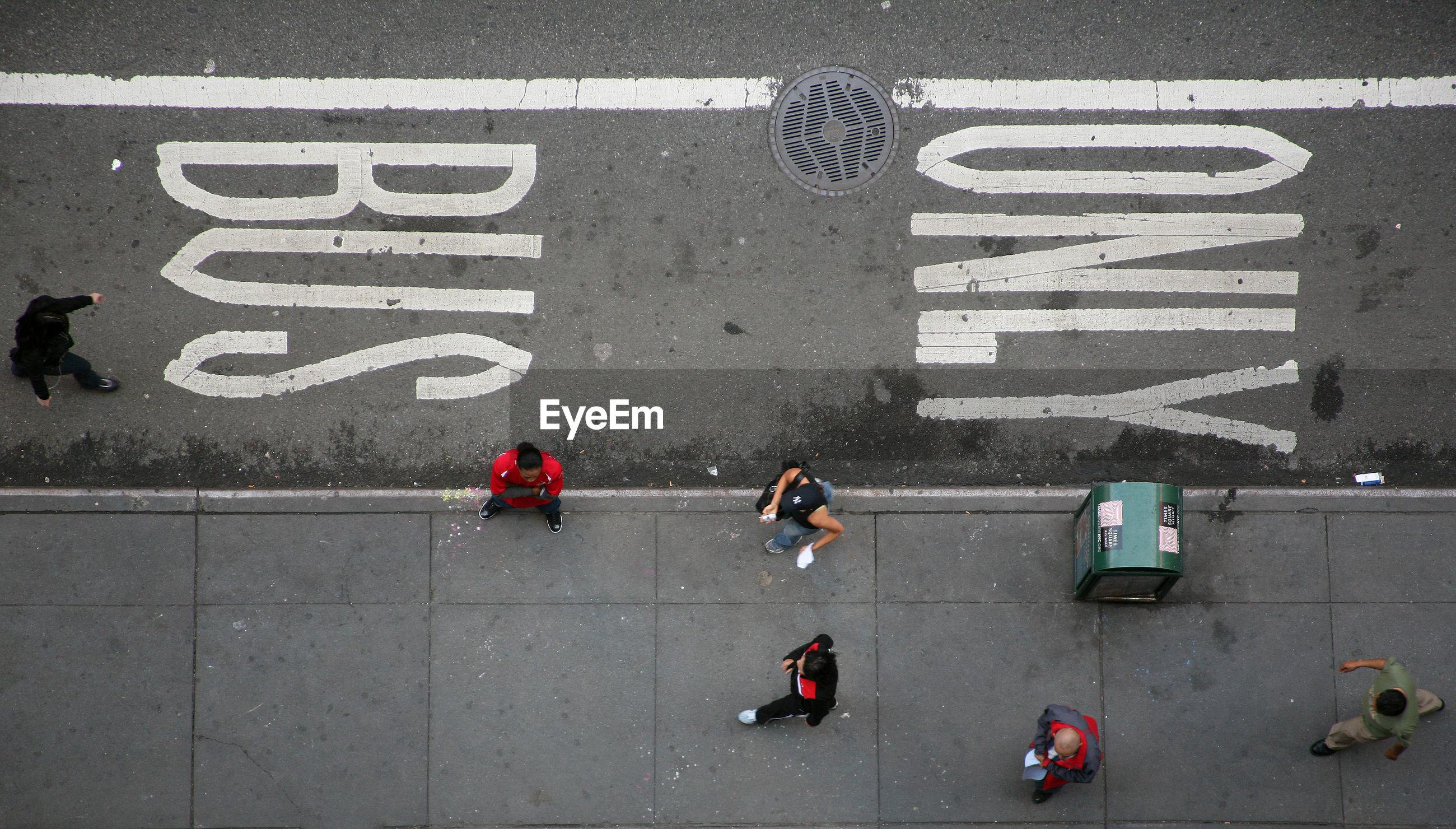 Directly above shot of people walking on sidewalk