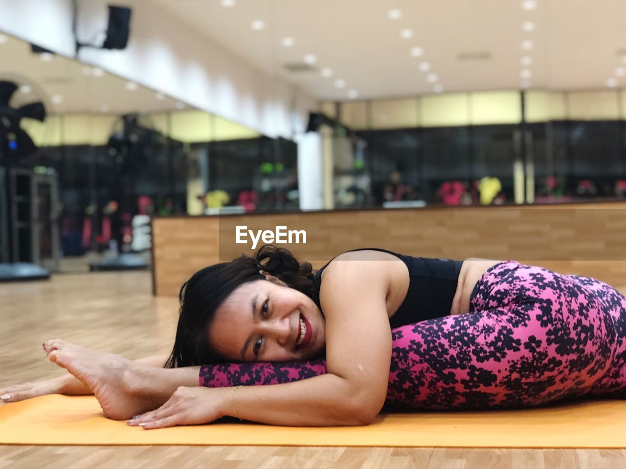 Side View Portrait Of Smiling Woman Exercising In Gym