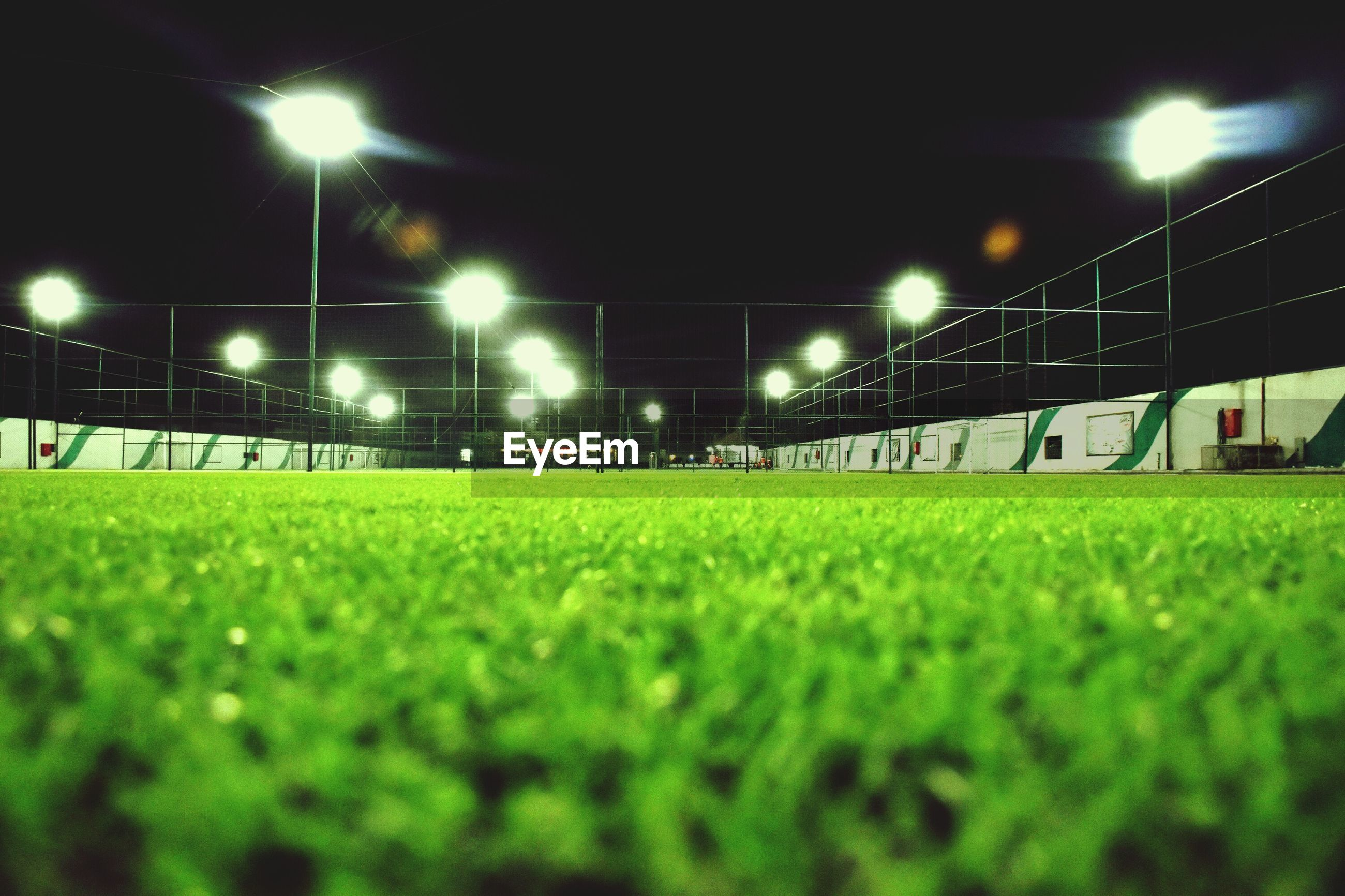 Surface level view of illuminated playing field at night