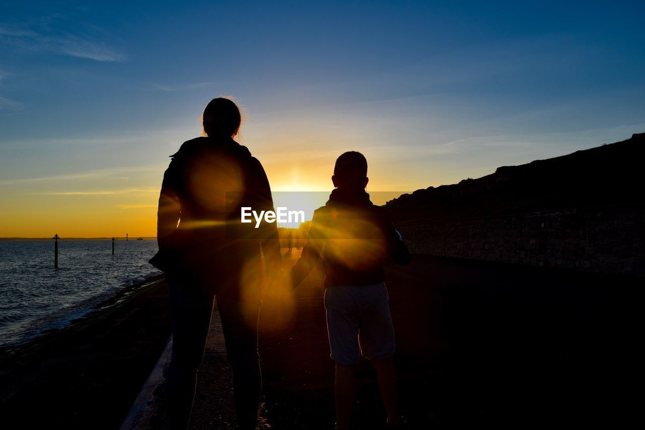 sky, sunset, two people, men, togetherness, real people, water, leisure activity, silhouette, standing, love, bonding, nature, beauty in nature, lifestyles, scenics - nature, males, sunlight, positive emotion, lens flare, sun, couple - relationship, outdoors, son