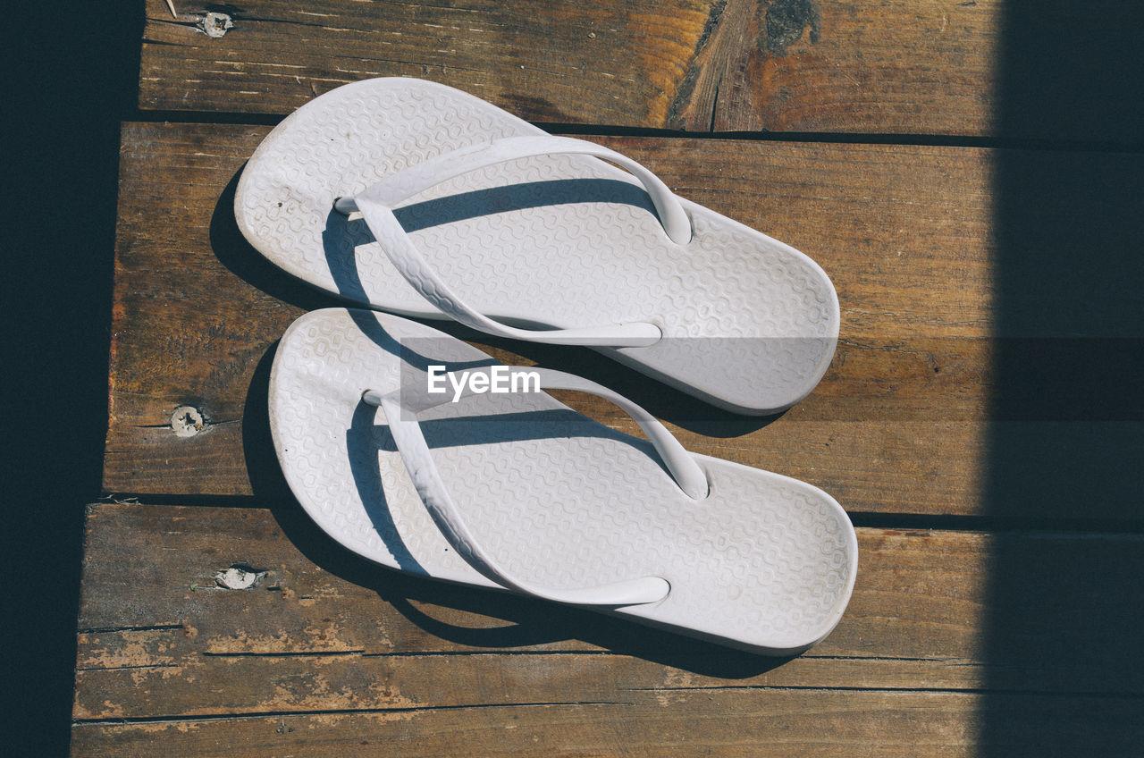 Directly above shot of flip-flops on boardwalk