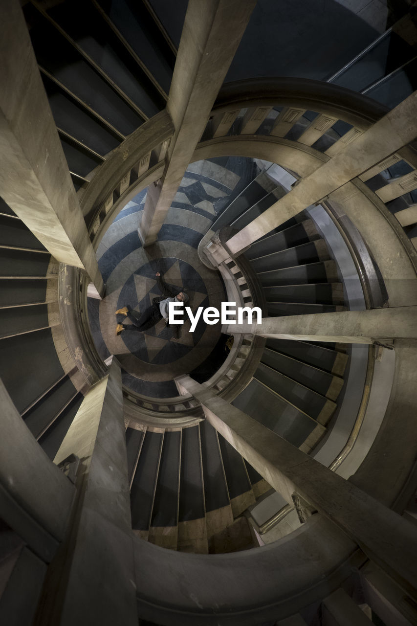 Directly above view of woman lying by spiral staircase in building