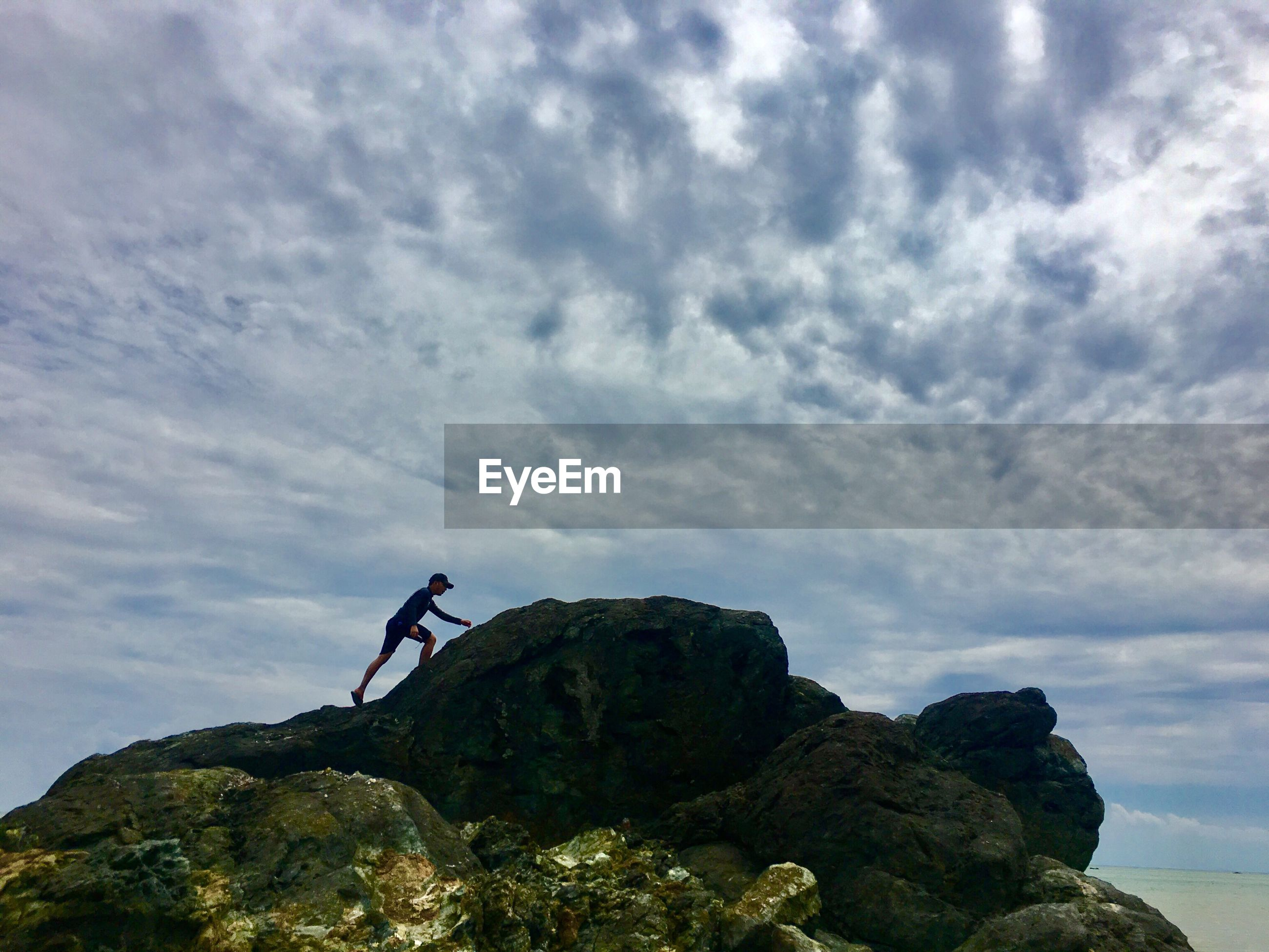 Low angle view of man climbing on rock against cloudy sky