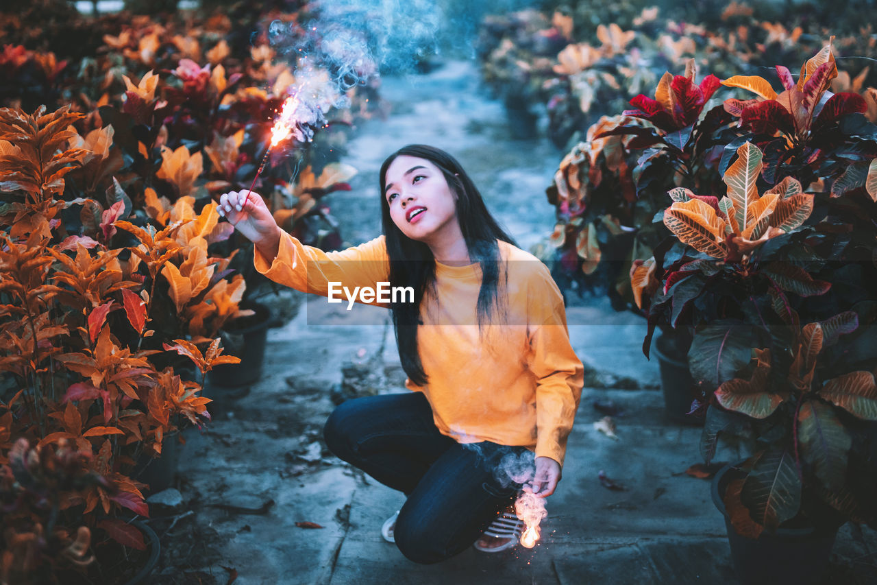 Full length of woman looking at burning firework amidst plants
